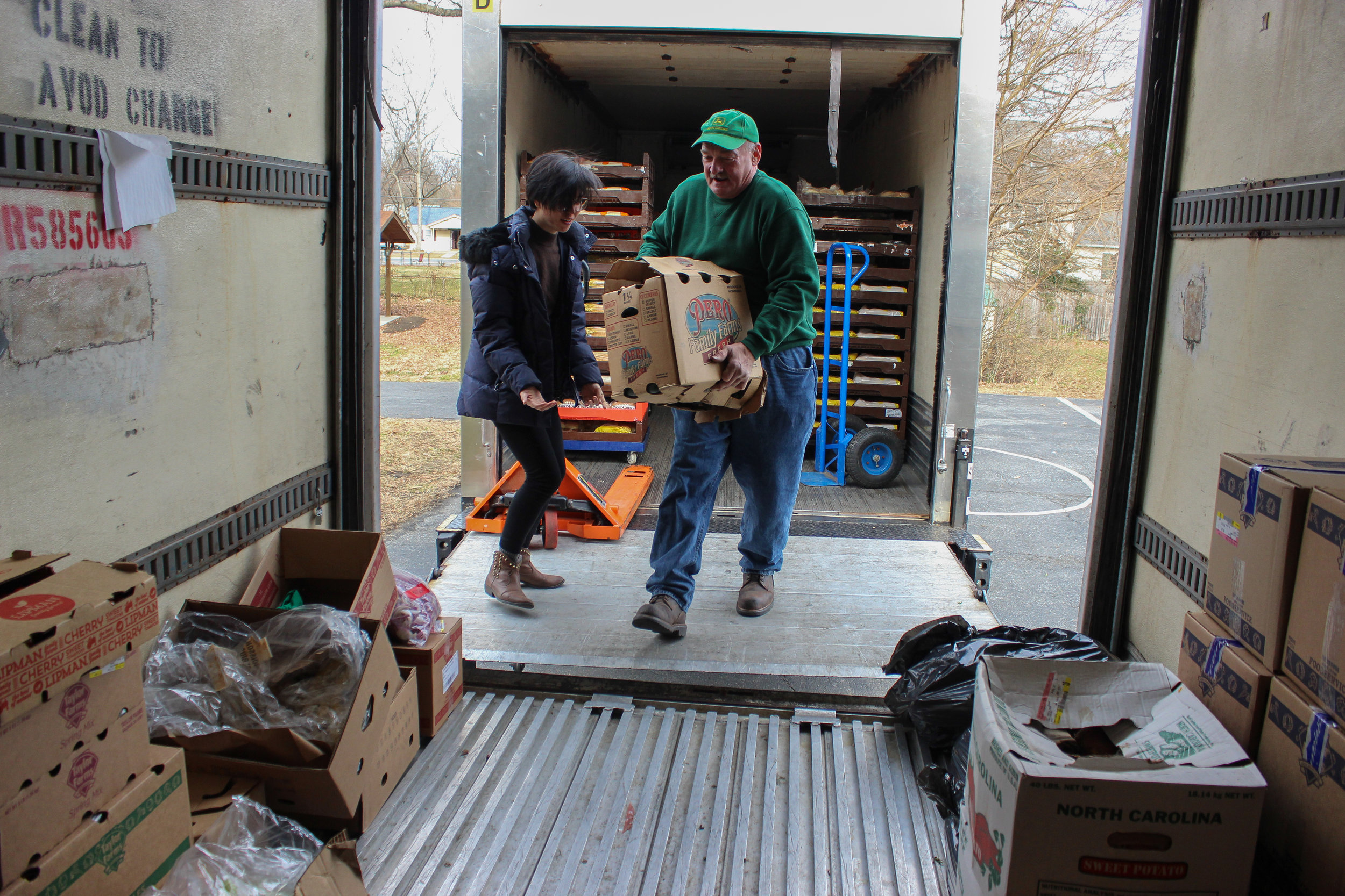 James, a volunteer at the Christian Life Center (CLC), moves the recovered food to CLC's refrigerated semi-trailer, with the help of Rosalyn Lam, our Program and Communications Fellow.