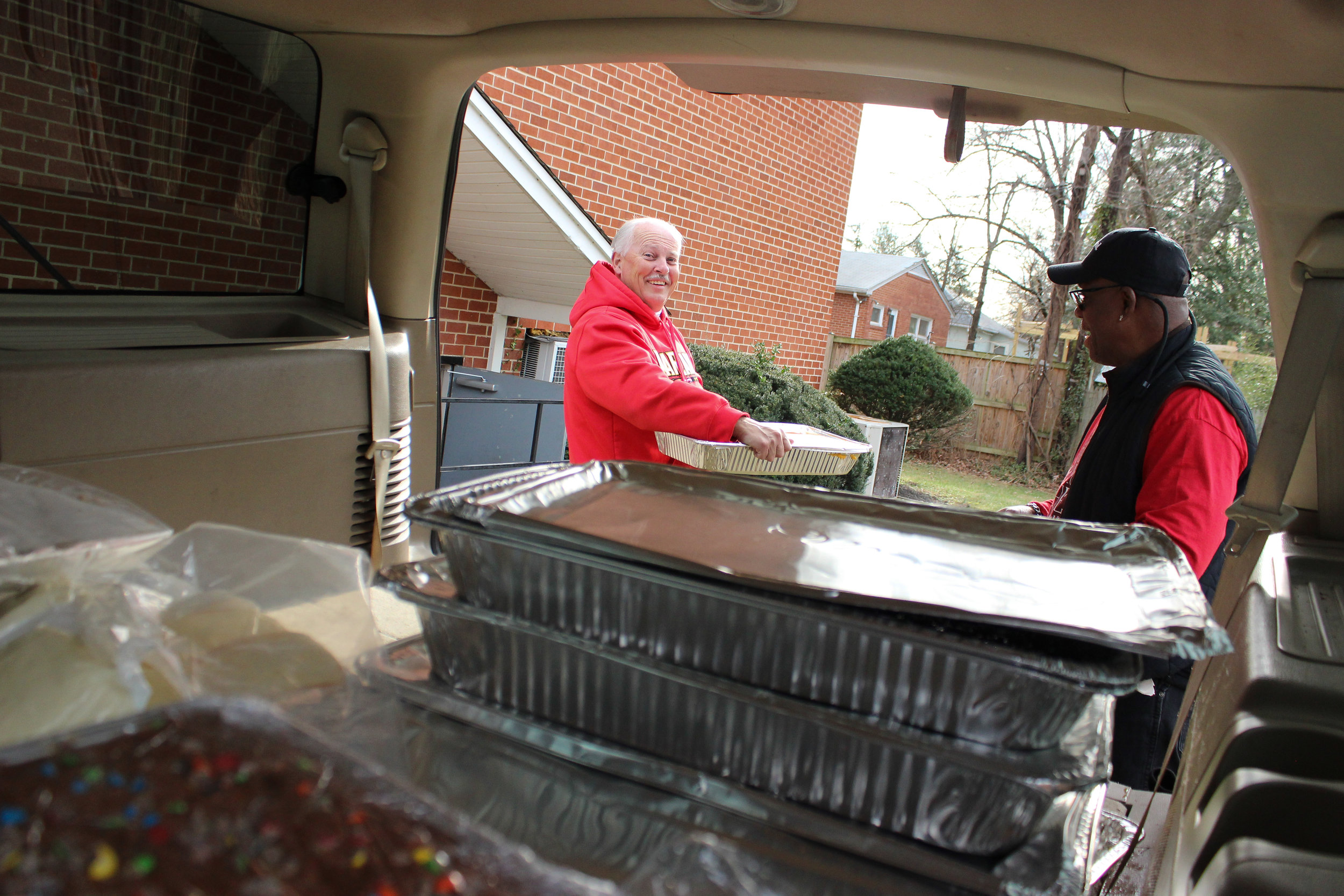 Pastor Ben (right) and Eric, who works closely with CLC's food pick-up and distribution program, unpack the van filled with surplus food.
