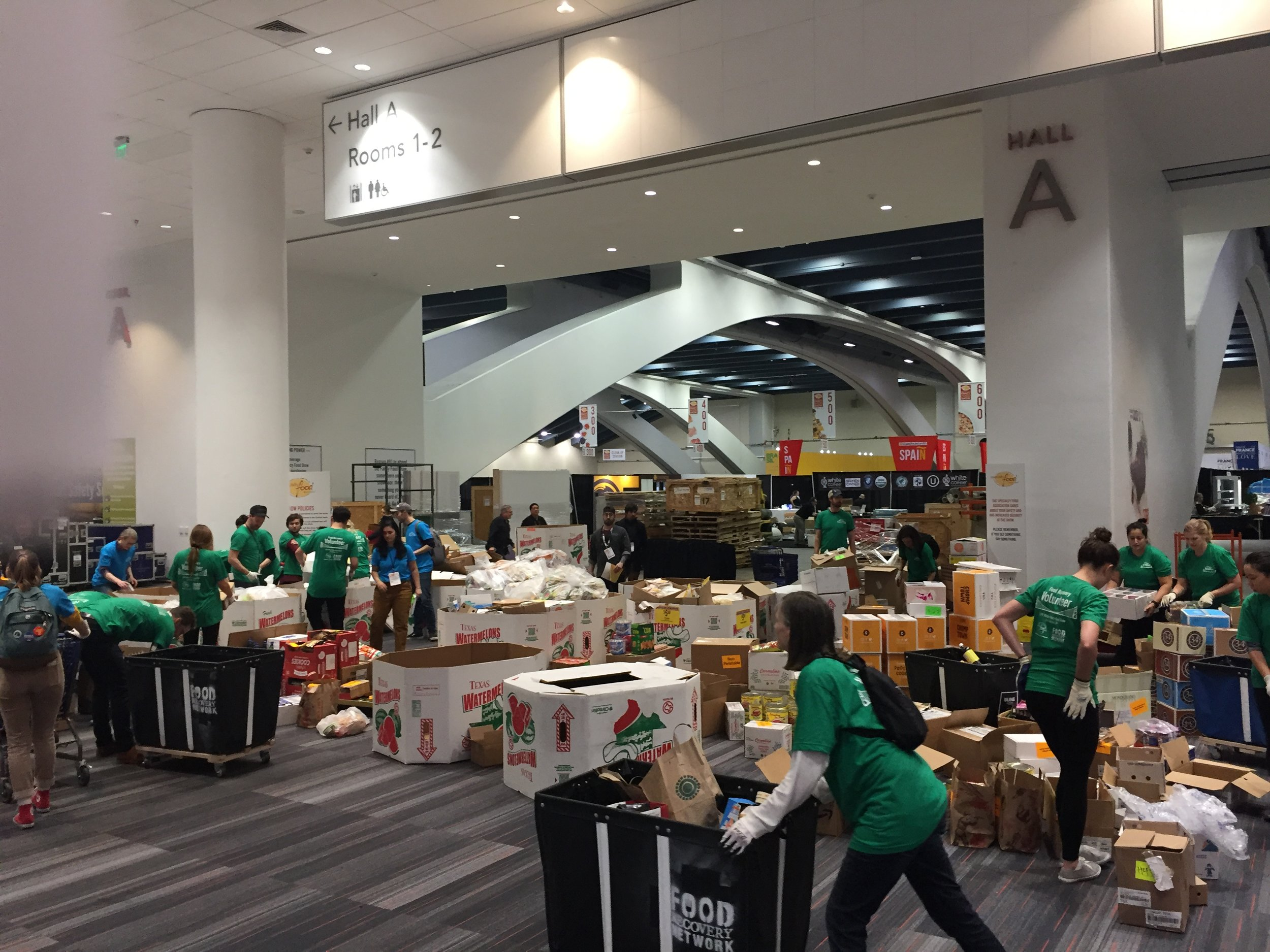 Volunteers bring recovered food from exhibit booths to consolidation zones, where food is packed into pallets for delivery to Delancey Street Foundation.