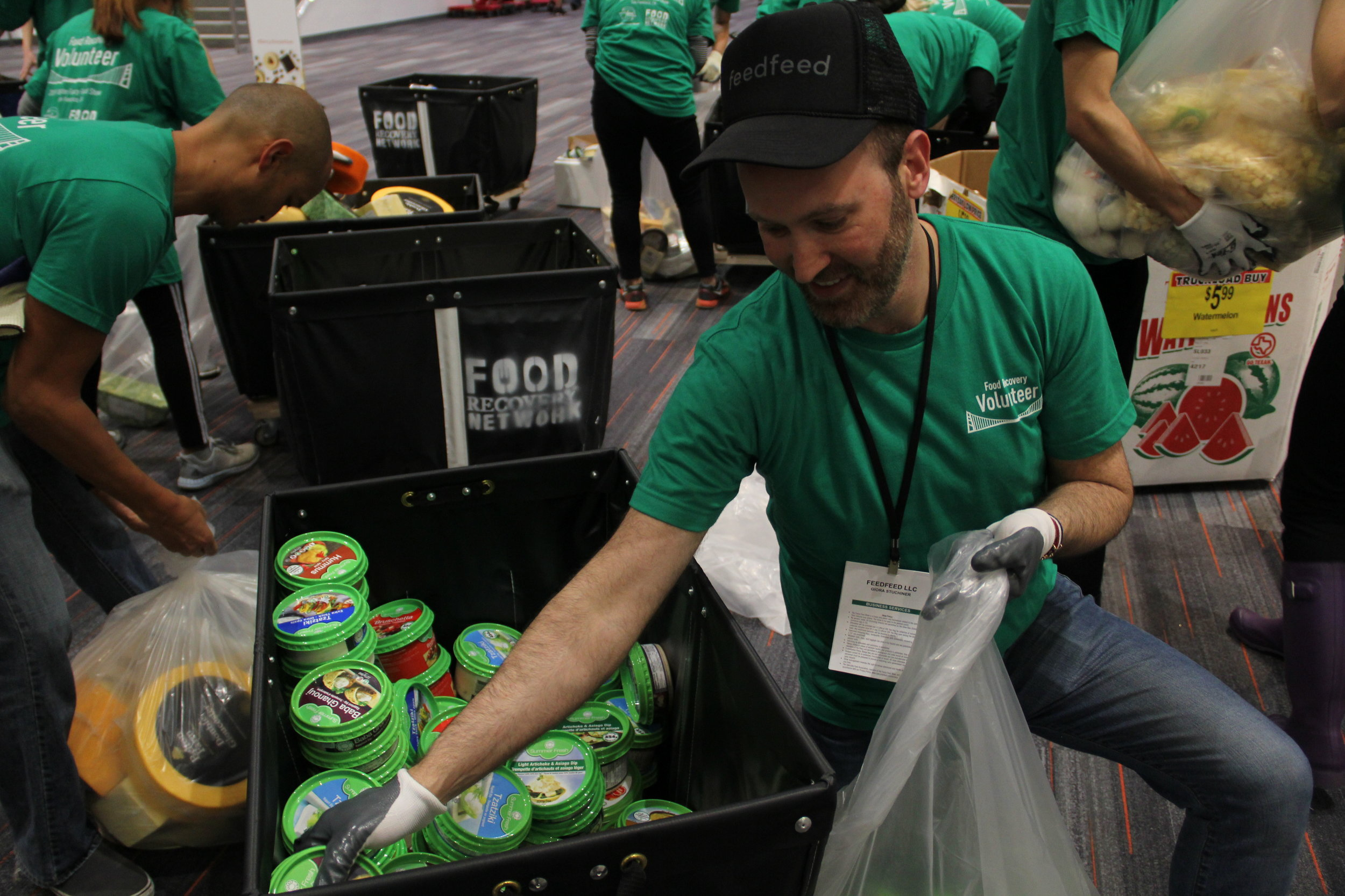 Giora Stuchiner, Art Director at Feedfeed, organizes perishable food items in the South Hall Consolidation Zone.