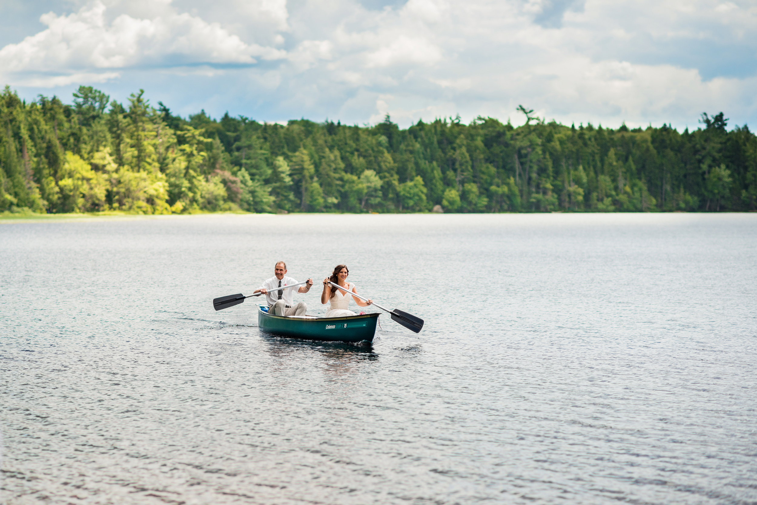 Father and Daughter padding in canoe to adirondack wedding ceremon