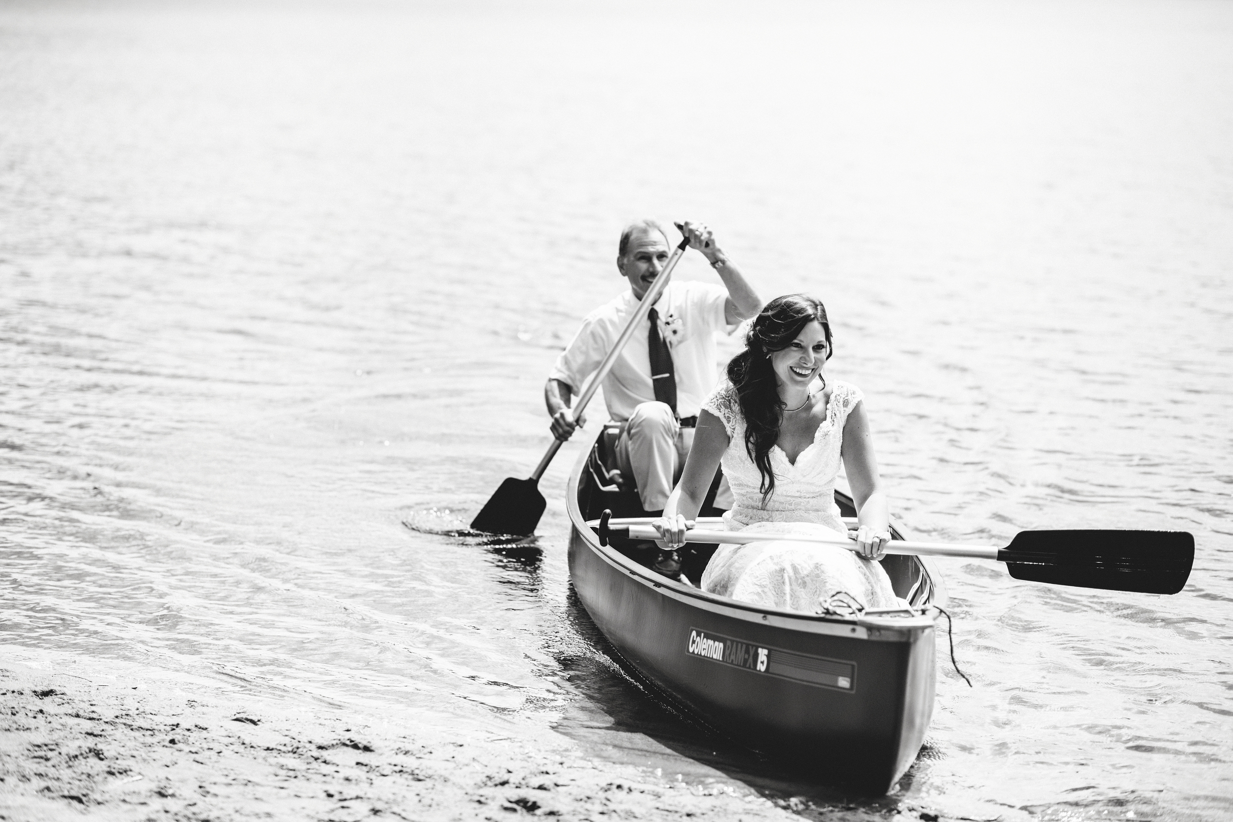 father daughter paddling in canoe to shore wedding ceremony