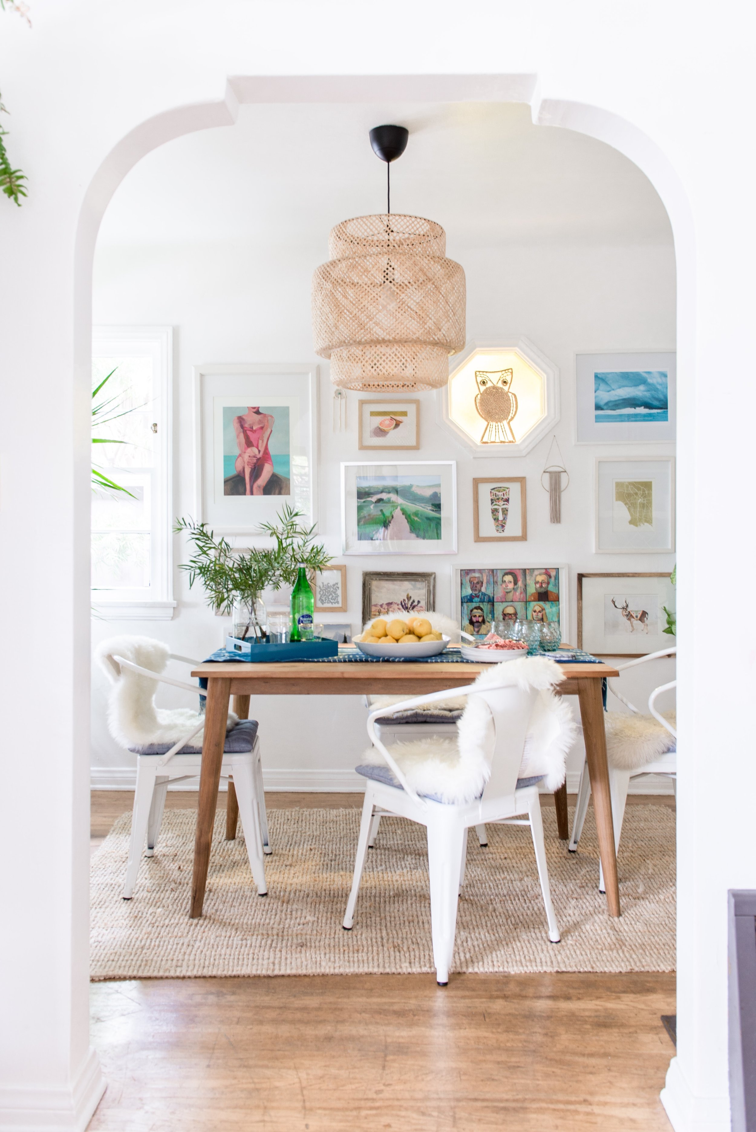 Dining room with table set, white chairs and a gallery wall.jpg