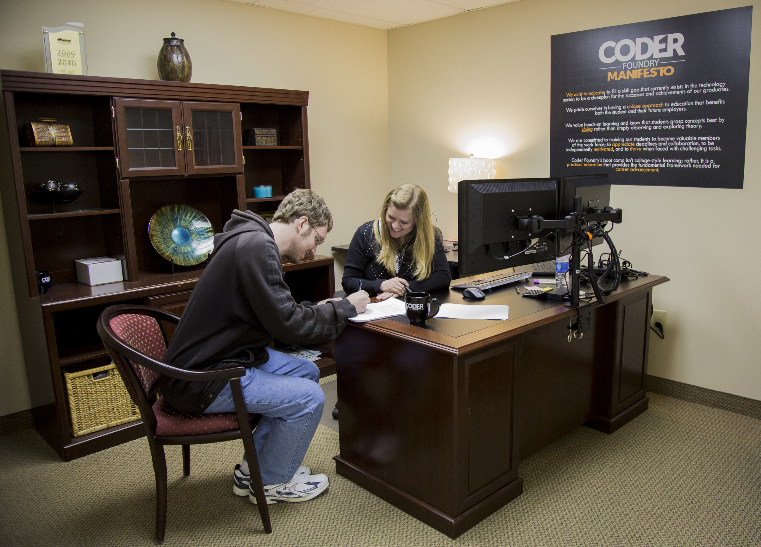 Keith Sturzengecker signing his acceptance letter with Natosha Sanders, head of Coder Foundry's Placement Services