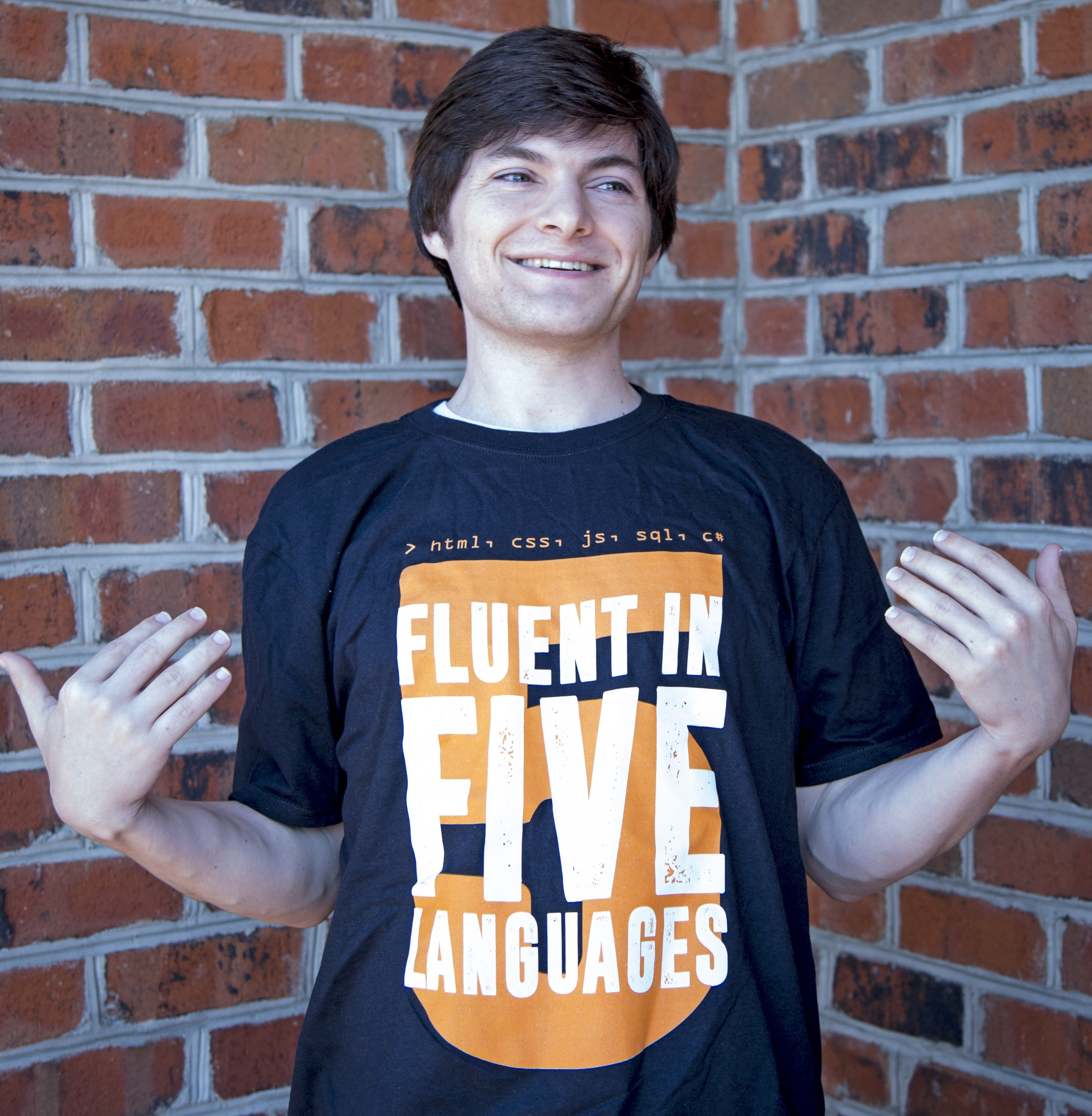 "Coder Foundry graduate, Kenneth R. showing off his graduation T-shirt, ""Fluent in 5 Languages"""