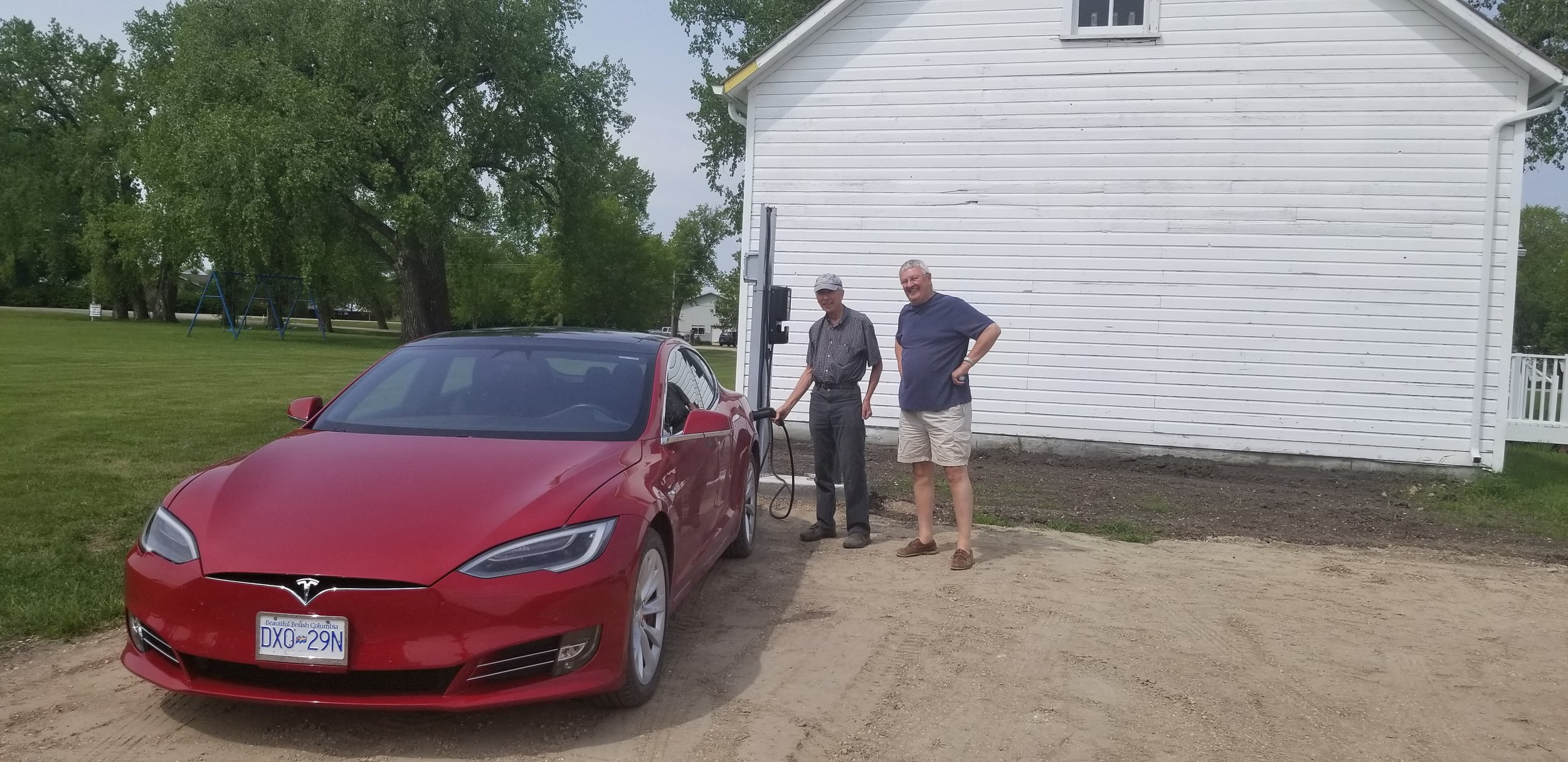 The first charge given to Roy Abrams' (right) electric powered Tesla vehicle by Ray Hamm (left), a member of the Neubergthal Heritage Foundation board, and main contact in the setting up of this station.