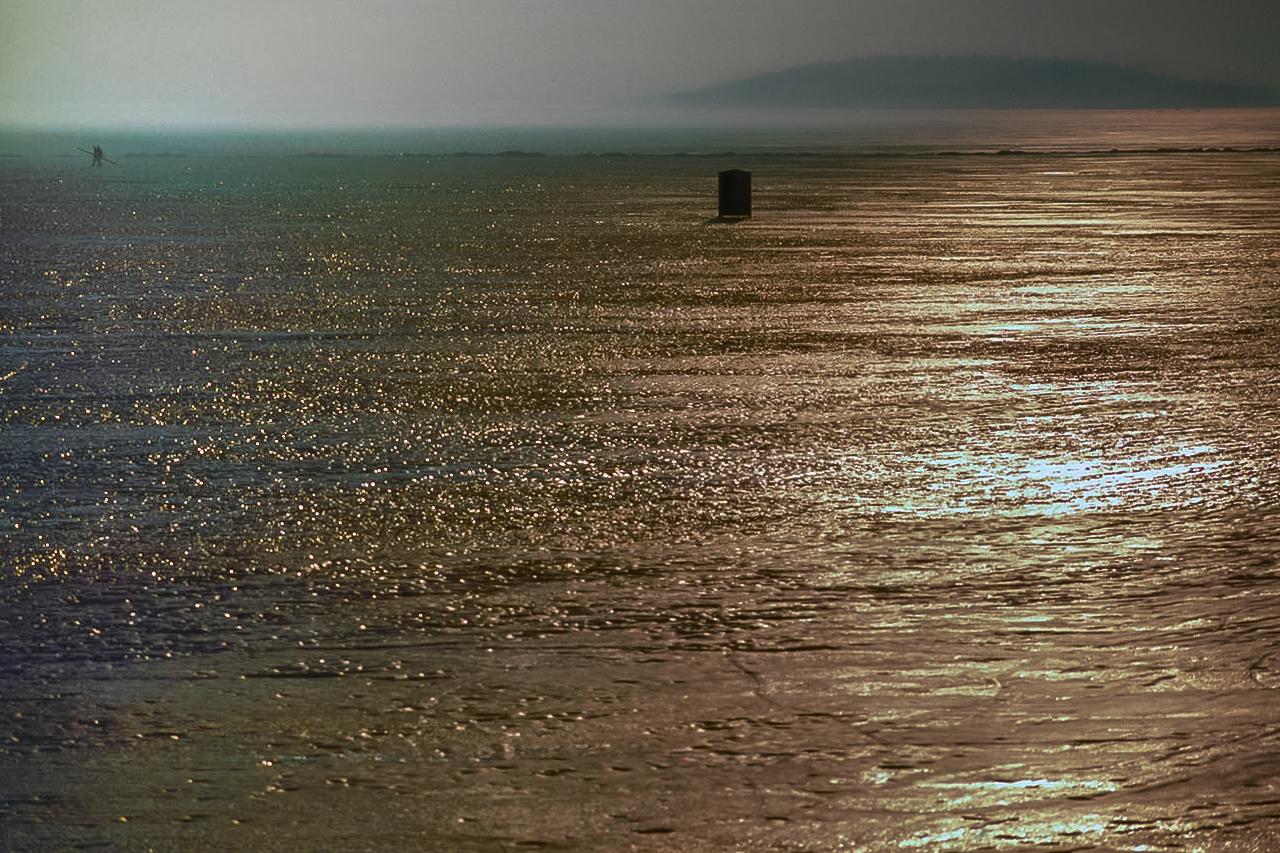 Last Two Fishermen Walk To Shore On Frozen Green Lake