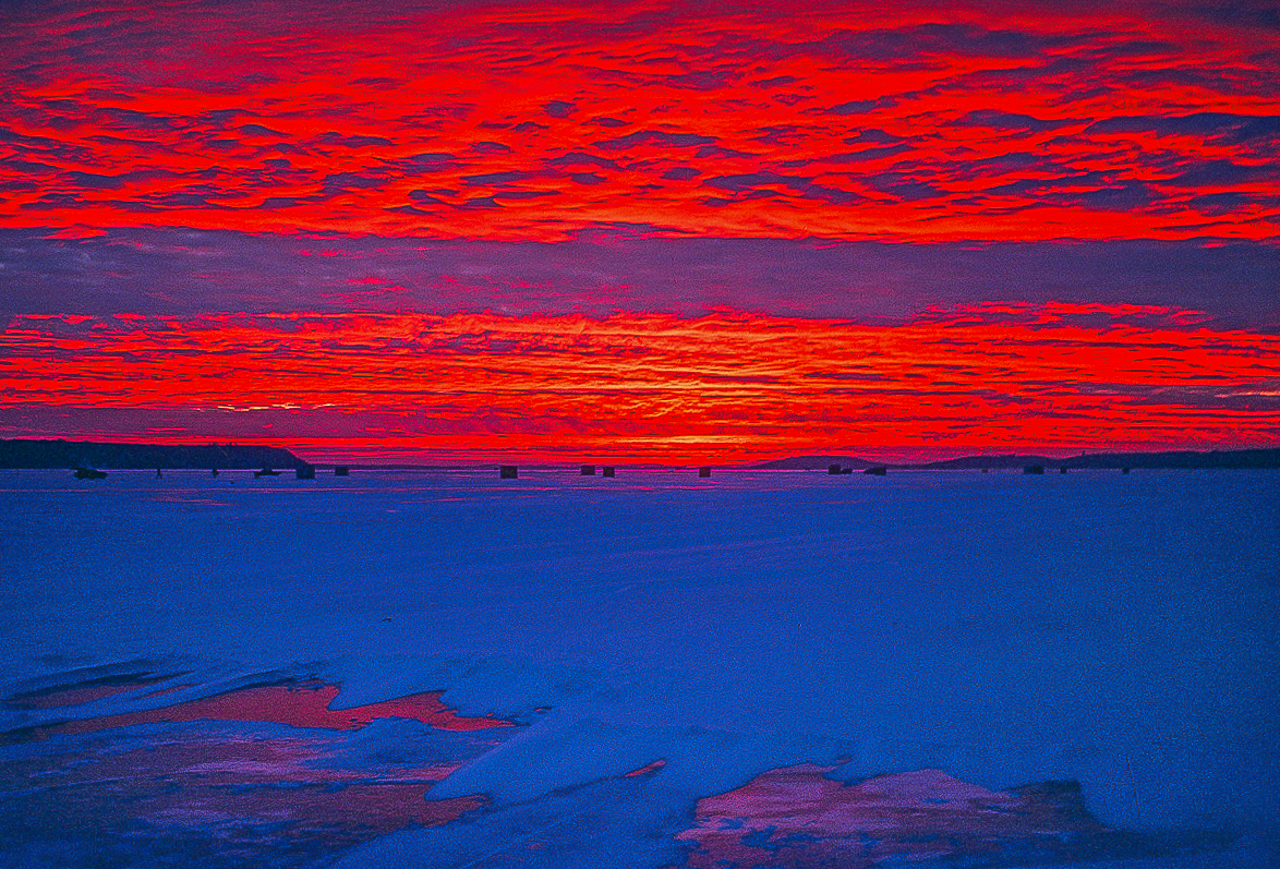 RED SUNSET BATHES GREEN LAKE ICE FISHING VILLAGE (1984)