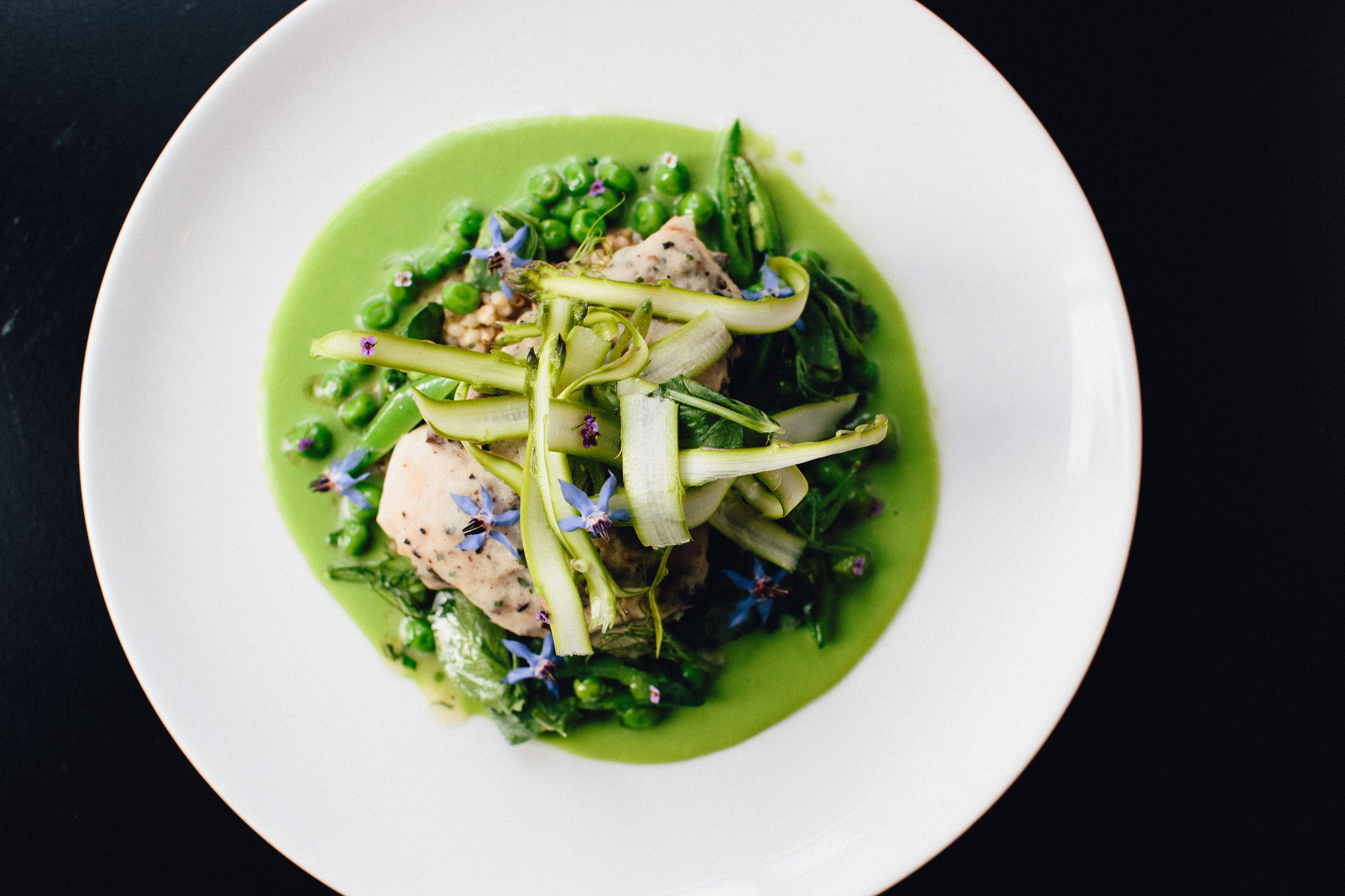 Steamed Red Snapper encrusted with a scallop & truffle mousse. Served over sorghum grains with a pea butter, spring peas, sugar snap peas, shaved raw asparagus, mint. Dressed with white balsamic vinaigrette.