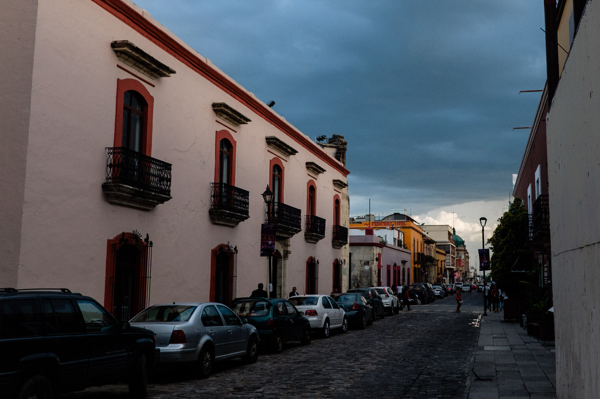 Throughout the late summer months, stormy rainy season in Oaxaca often paints the sky with dramatic dark blue and charcoal backdrops, creating a heightened effect where the already brightly colorful facades of the historic streets glow.