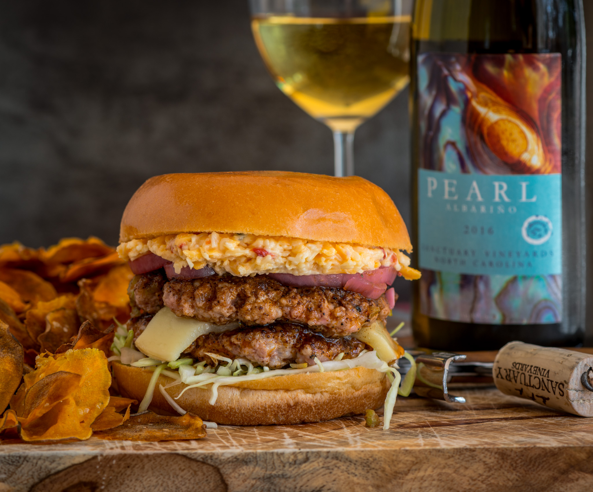 """VinoBurger, Eastern North Carolina version : Pork with a BBQ spice rub, pimento cheese, Taleggio-style cheese from Boxcarr Farms, pickled red onion, cabbage slaw, sweet potato chips, Sanctuary Vineyards """"Pearl"""" Albariño"""