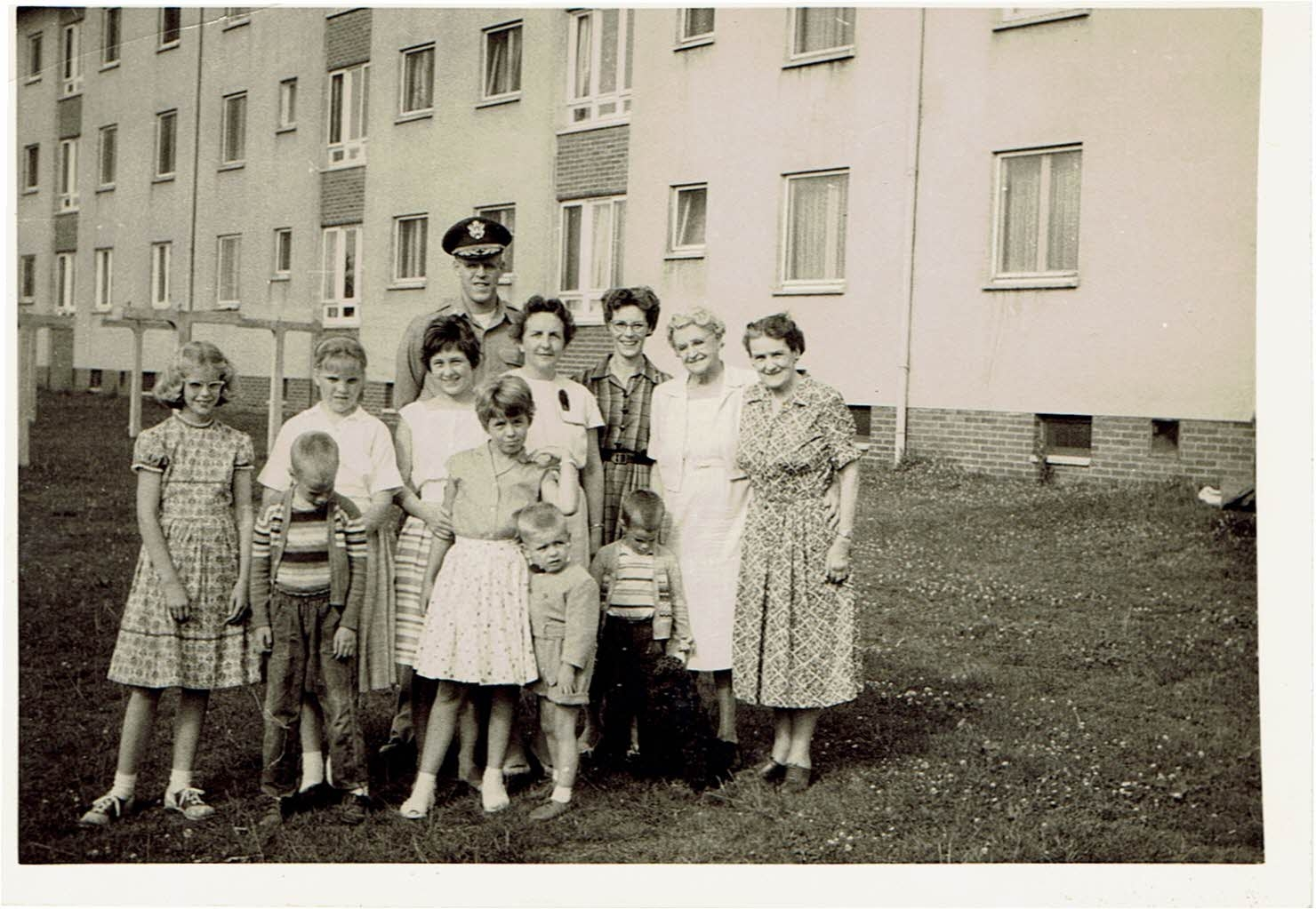 Our extended family in front of our quarters in Landstuhl, Germany, 1960.My father is wearing his hat. I'm on the left, dressed up in saddle shoes.