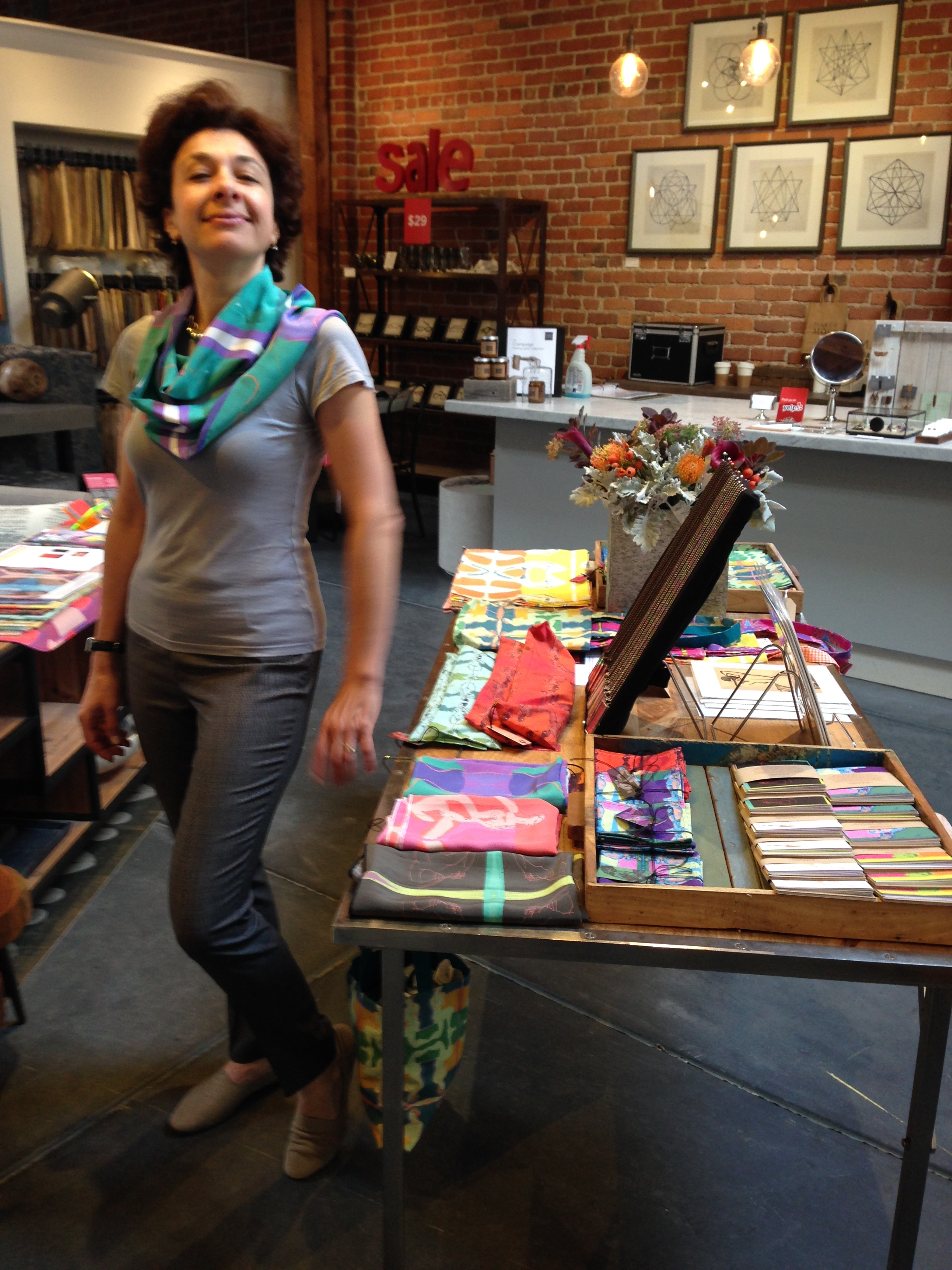 Valerie striking a pose in one of my art silk scarves. And check out the tables filled with my colorful. table linens, greeting cards, necklaces, gift wrap, tote bags, and more...