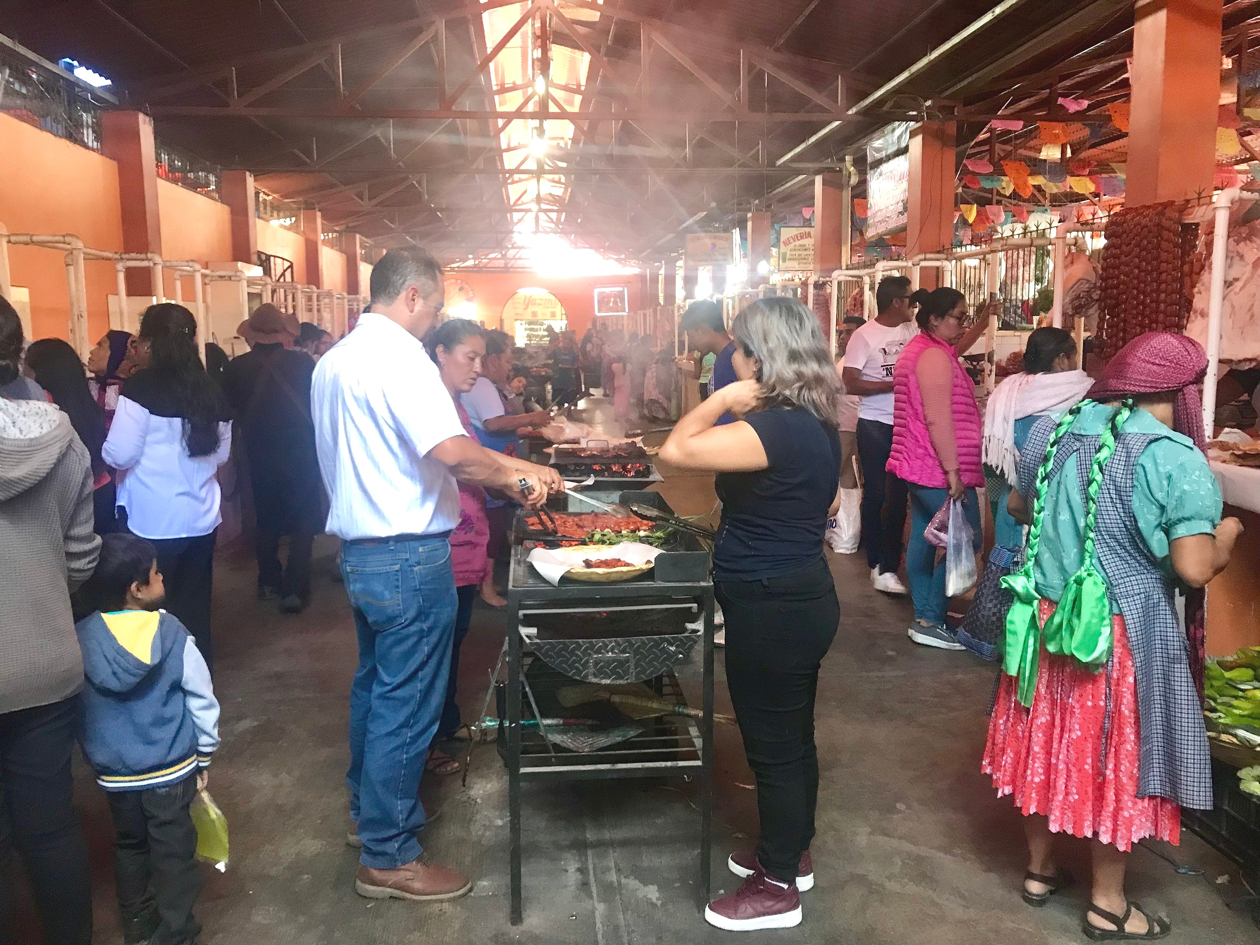 I admit I love her ribboned braids (right), although they were a common sight in this very Indian market outside of the city of Oaxaca with people cooking meat on open flames in the middle.