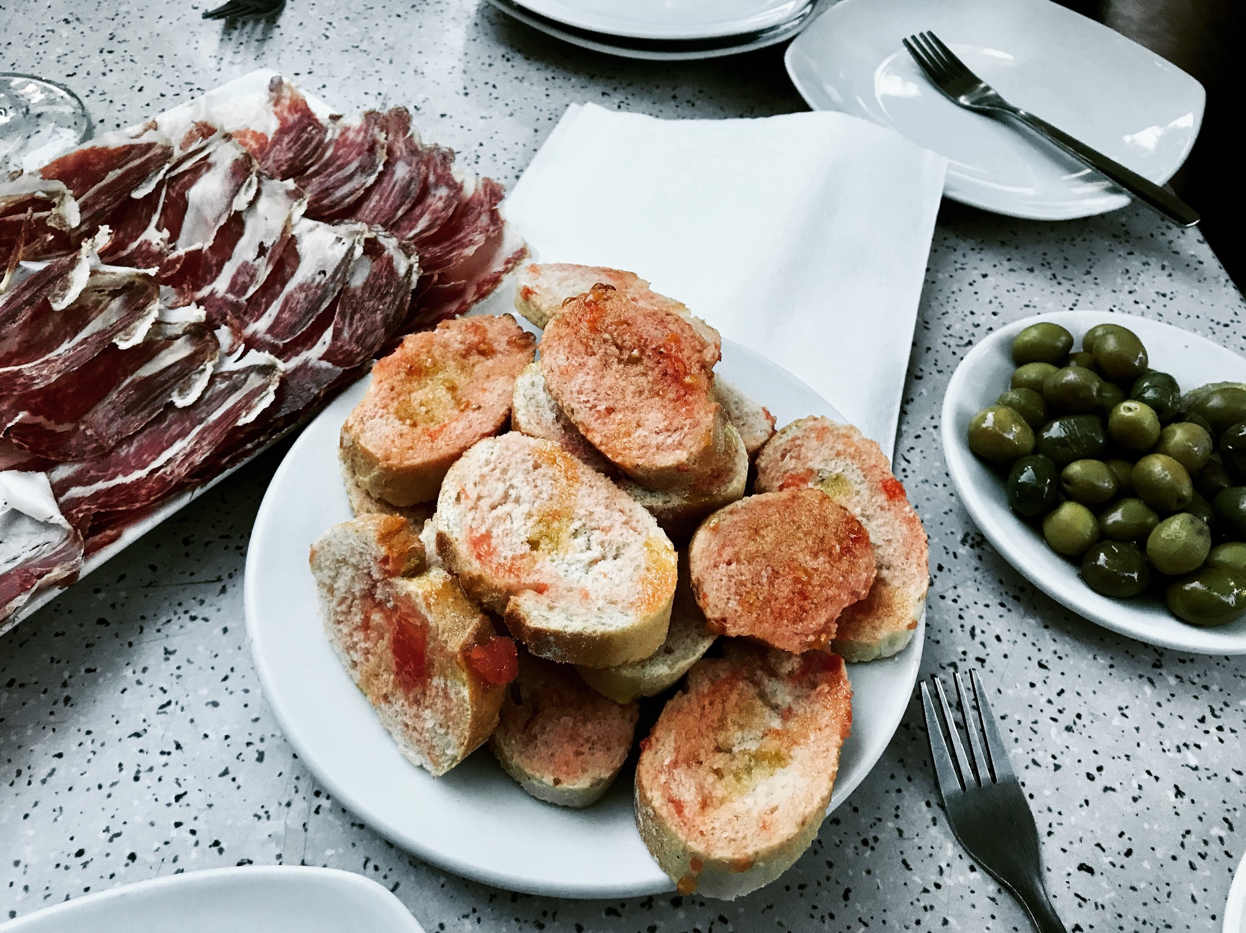 The other classic snacks to go with our drinks - Pa amb tomàquet, assorted olives, and a pile of jamon.