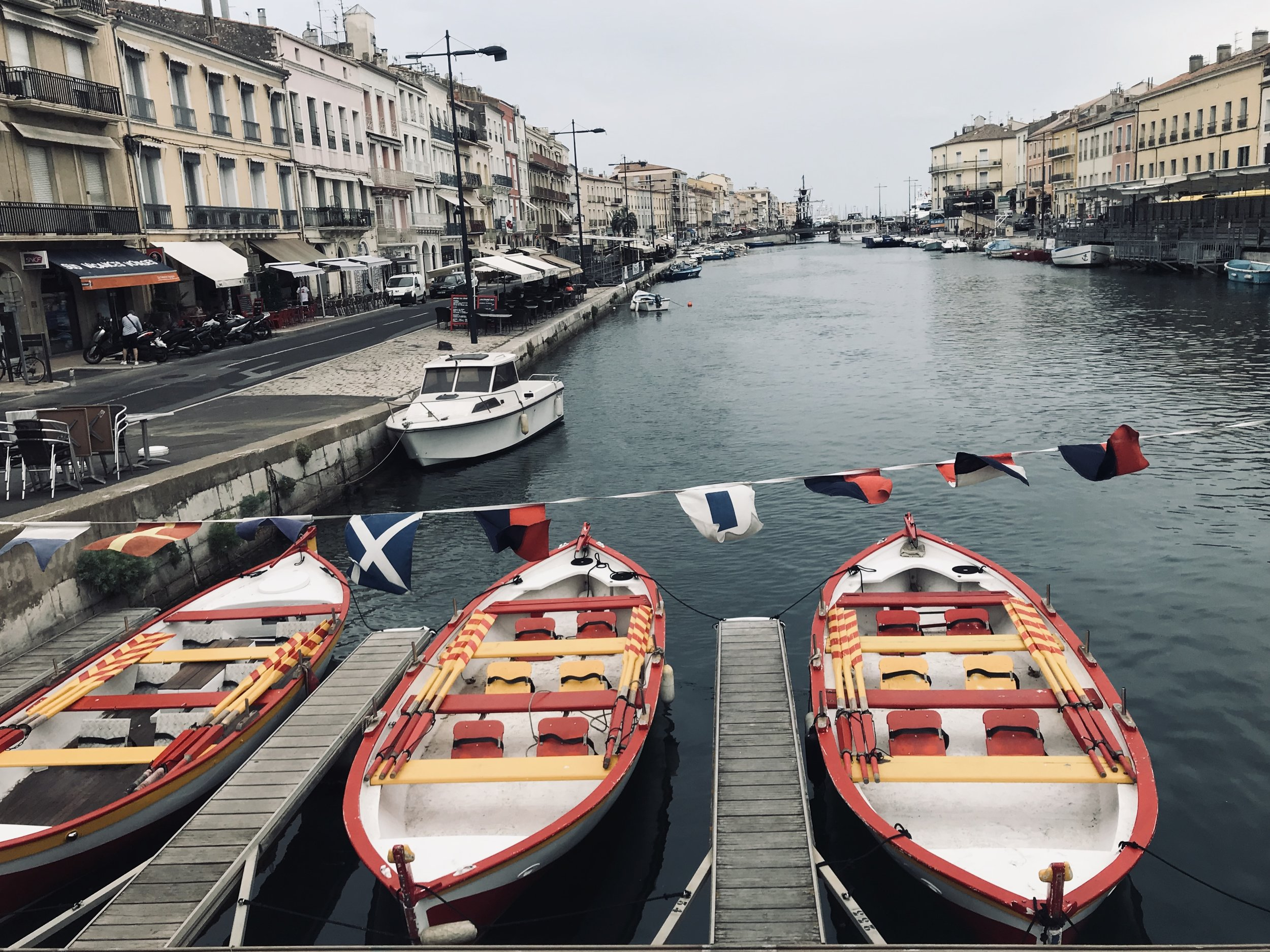 One of the scenic views of a Sete canal with colorful touring boats.