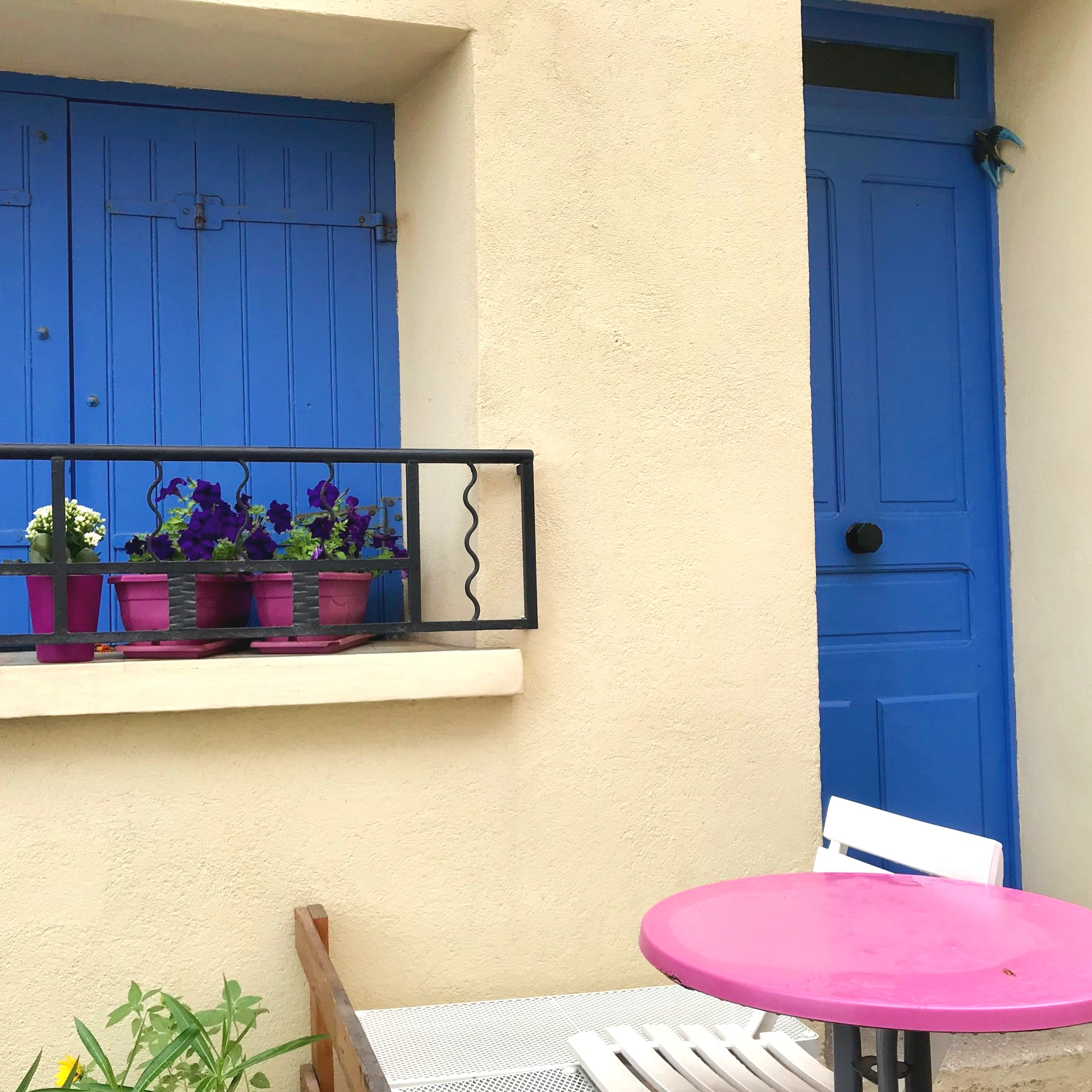 A manicured French house of ultramarine blue and rose pink with a creamy background. Yum!