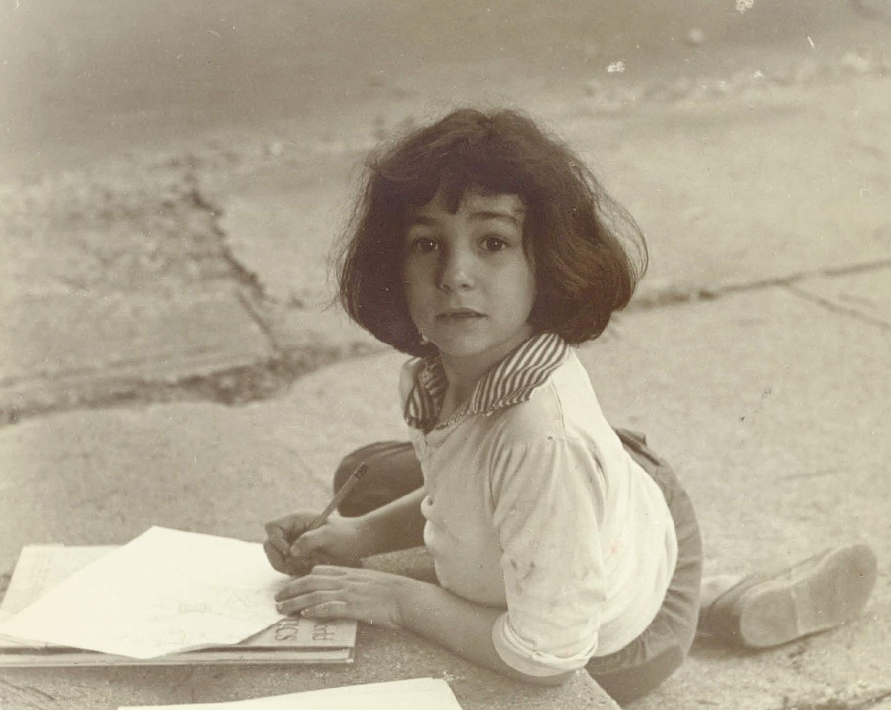 Old photo of me drawing in front of our house.