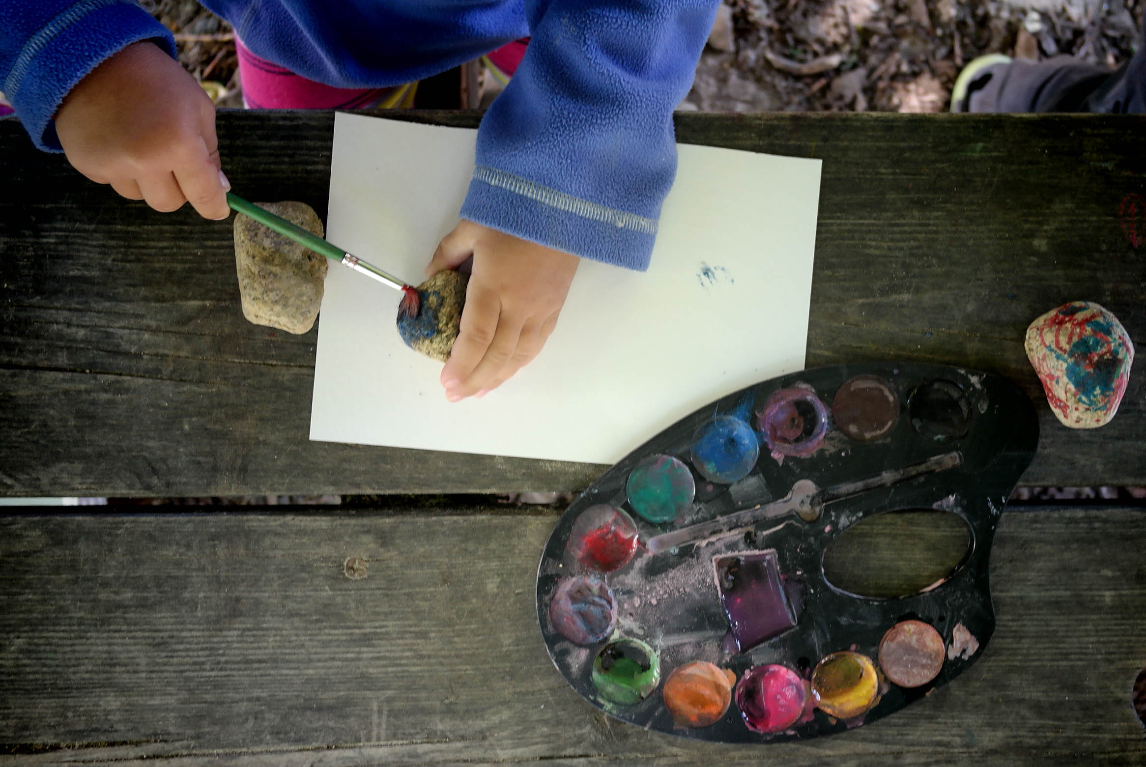 Toddlers painting rocks on the playground at The Breakwater School.