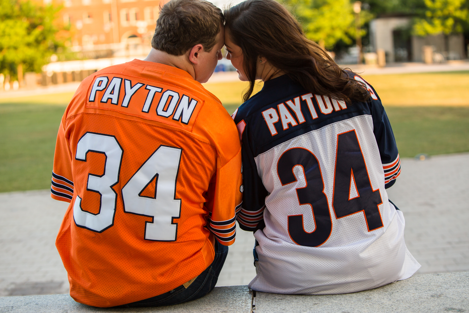 What a great idea to use his favorite sports jerseys for their engagement session.