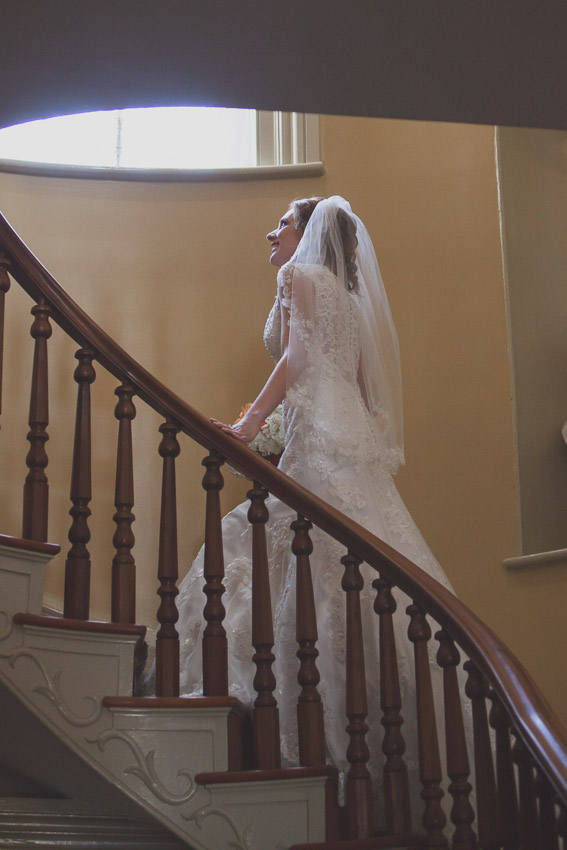 Bride climbing stairs for first look at Oaklands Mansion