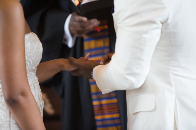 groom putting ring on brides hand
