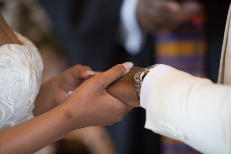 Bride putting grooms ring on