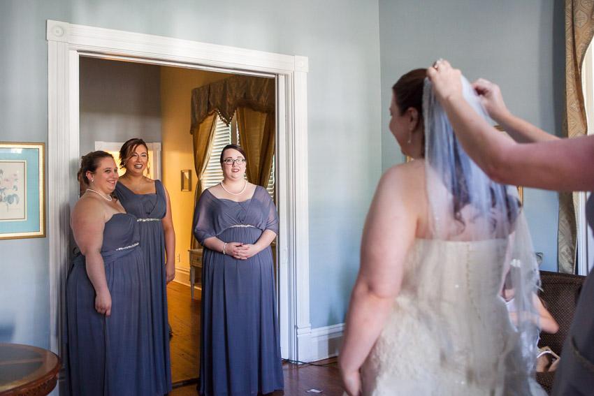 Bridesmaids smiling at Bride