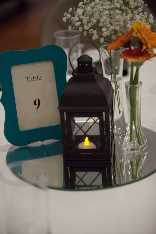 Lanterns used with frames and flowers on the table are a simple but beautiful option for table centerpieces