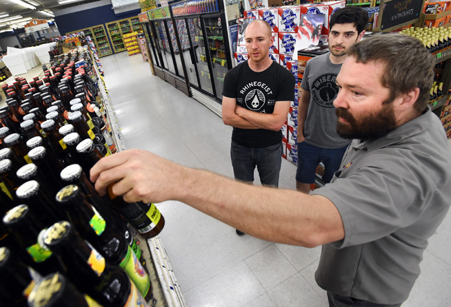 Kippie Loughlin, right, of Liquor Mart in Boulder, helps Michael Geramita, left, and Anthony Baraff, buy a 6-pack of assorted craft beers on Friday. (Cliff Grassmick Staff Photographer)
