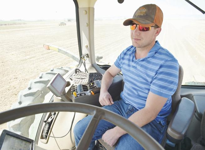 Scott Schlagel uses GPS-controlled auto steer in his John Deere tractor to plant sugar beets in a 110-acre field south of Longmont Wednesday - (Lewis Geyer / For the Camera)