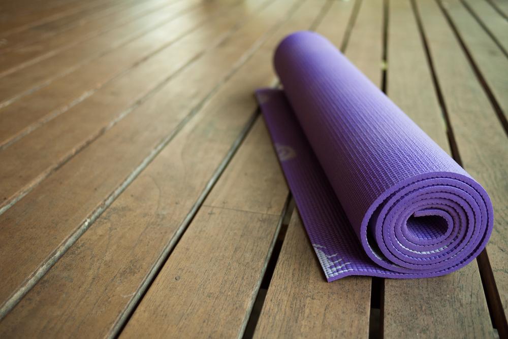 Purple yoga mat on wooden floor
