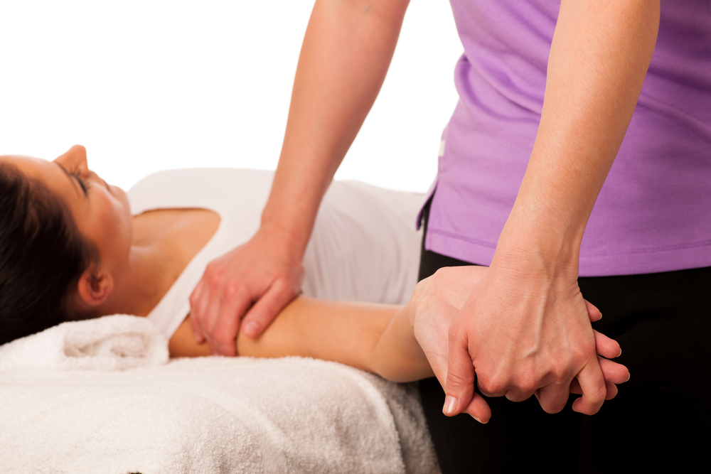 Physiotherapist performing treatment on female patient's shoulder