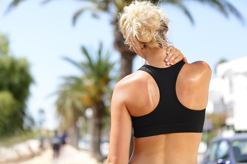 Woman massaging her neck to relieve pain from jogging
