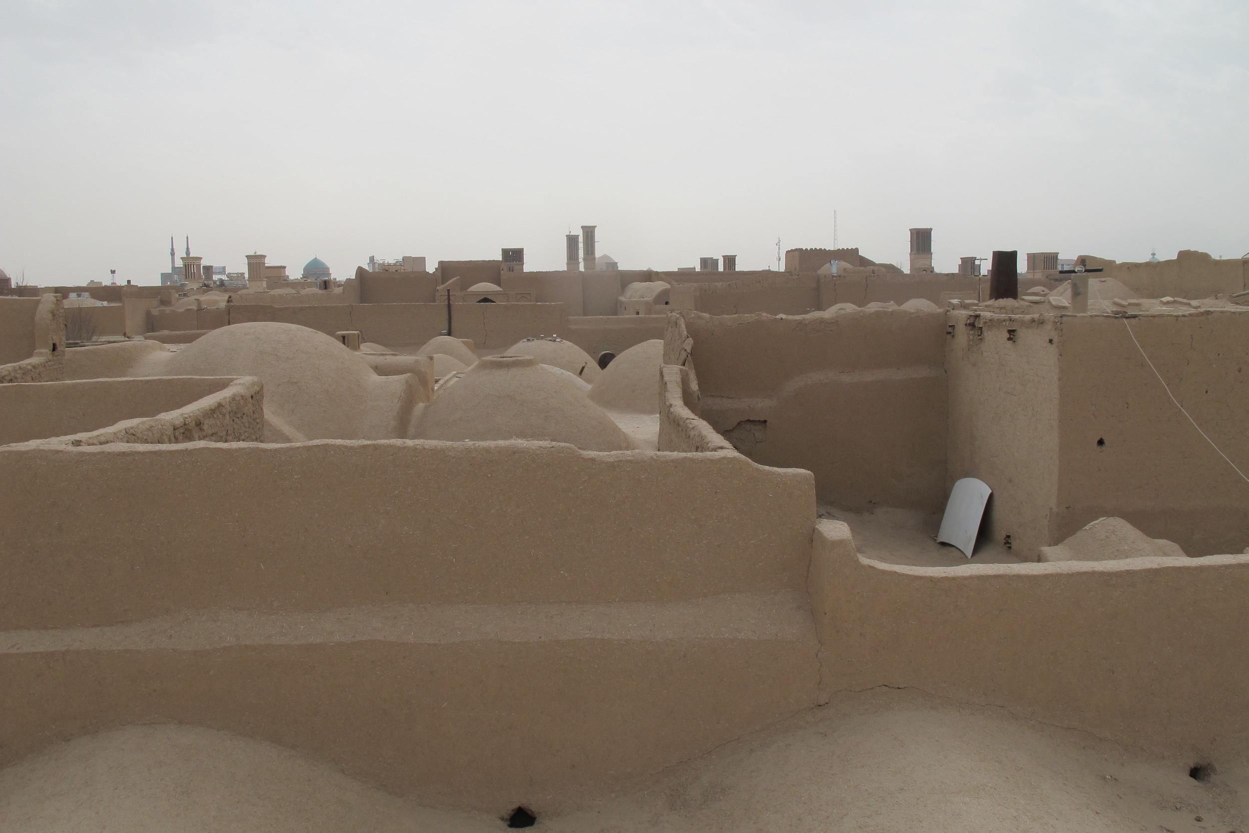 Vy över Yazd – en stad i soltorkad lera, där vindtornen höjer sig i bakgrunden. Foto: Bitte Hammargren