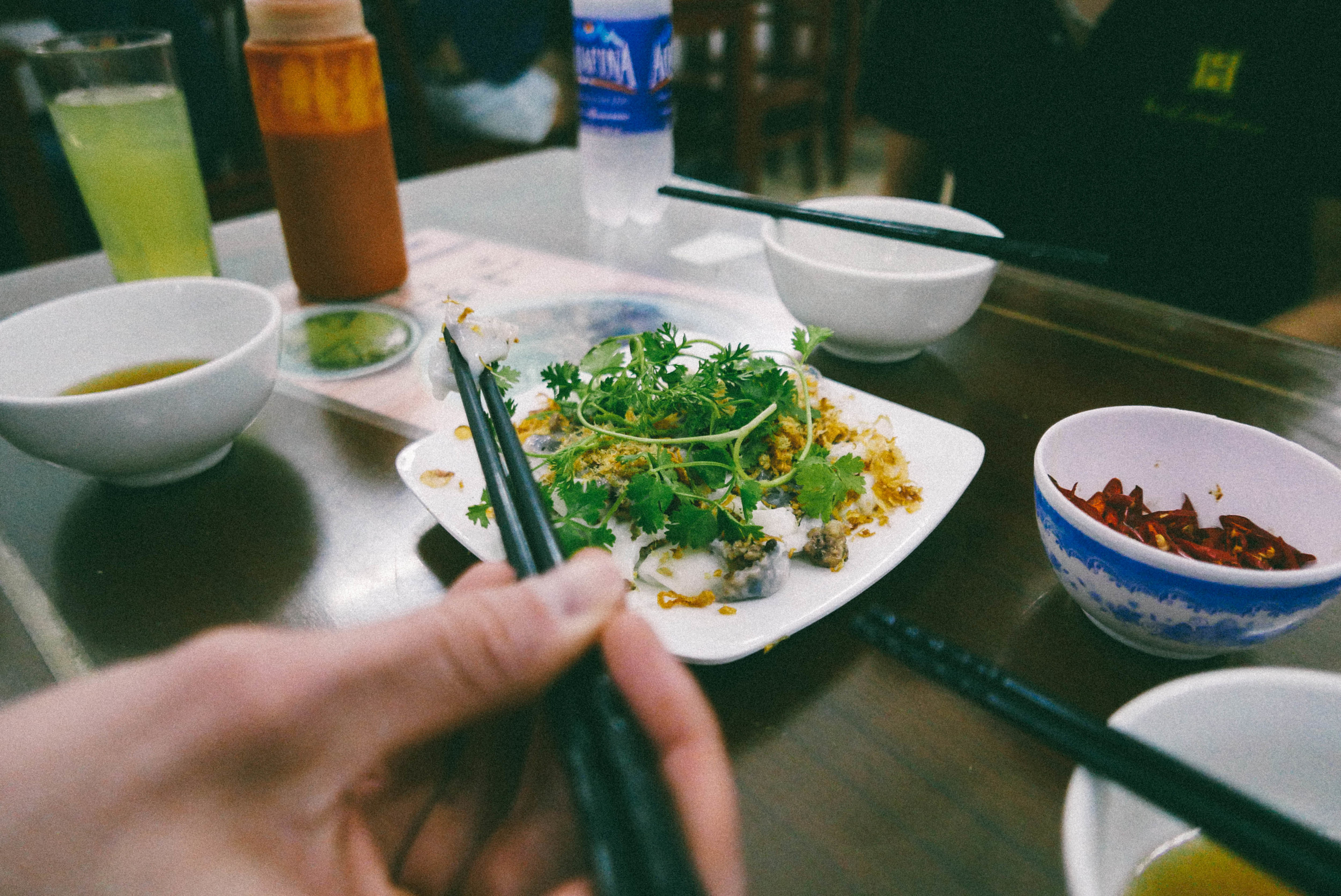 Digging into a plate of banh cuon.