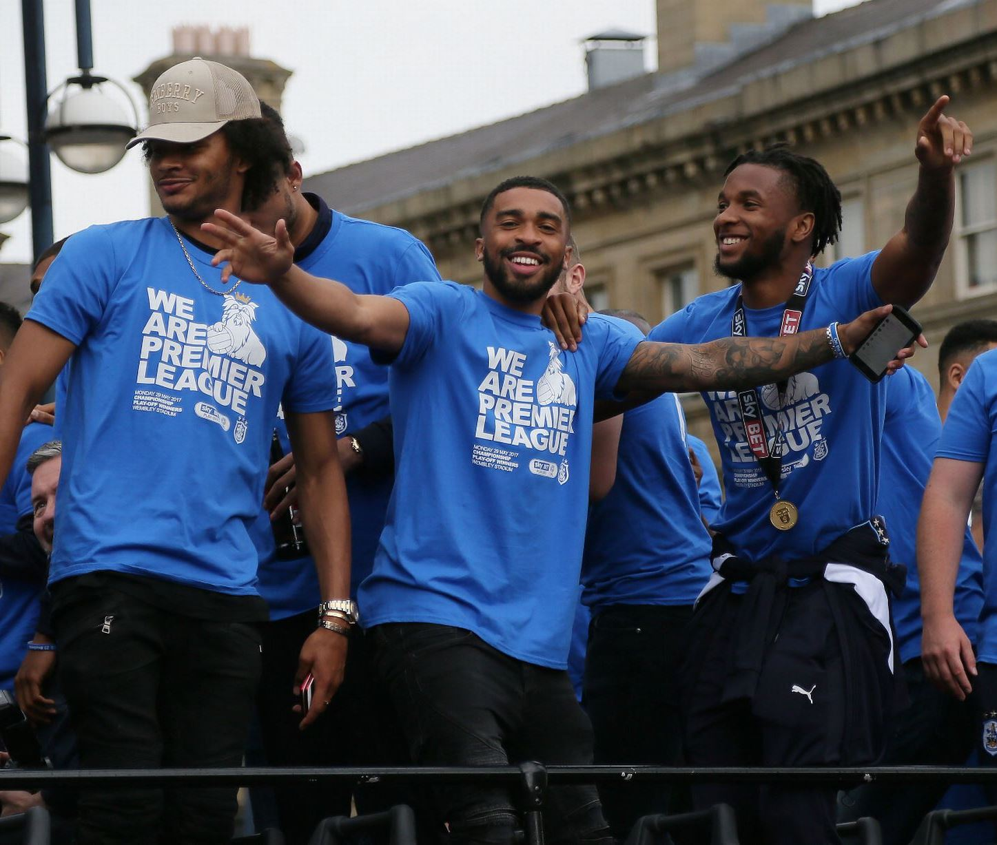 Left to right: Izzy Brown, Tareiq Holmes-Dennis and Kasey Palmer celebrate during parade ceremony