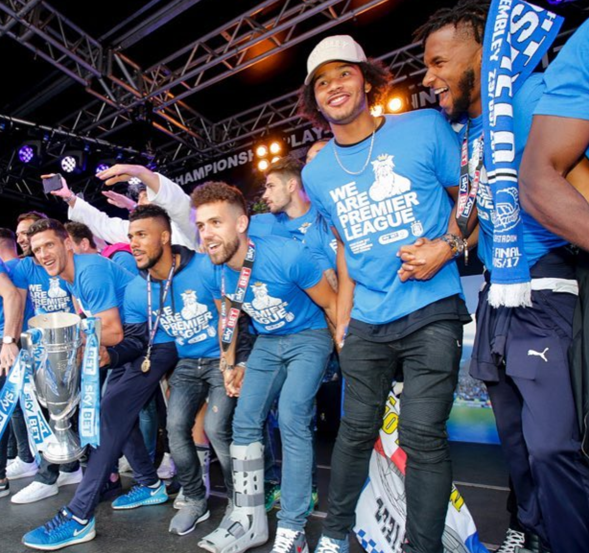 Huddersfield Town Players on stage at local Town Hall with trophy