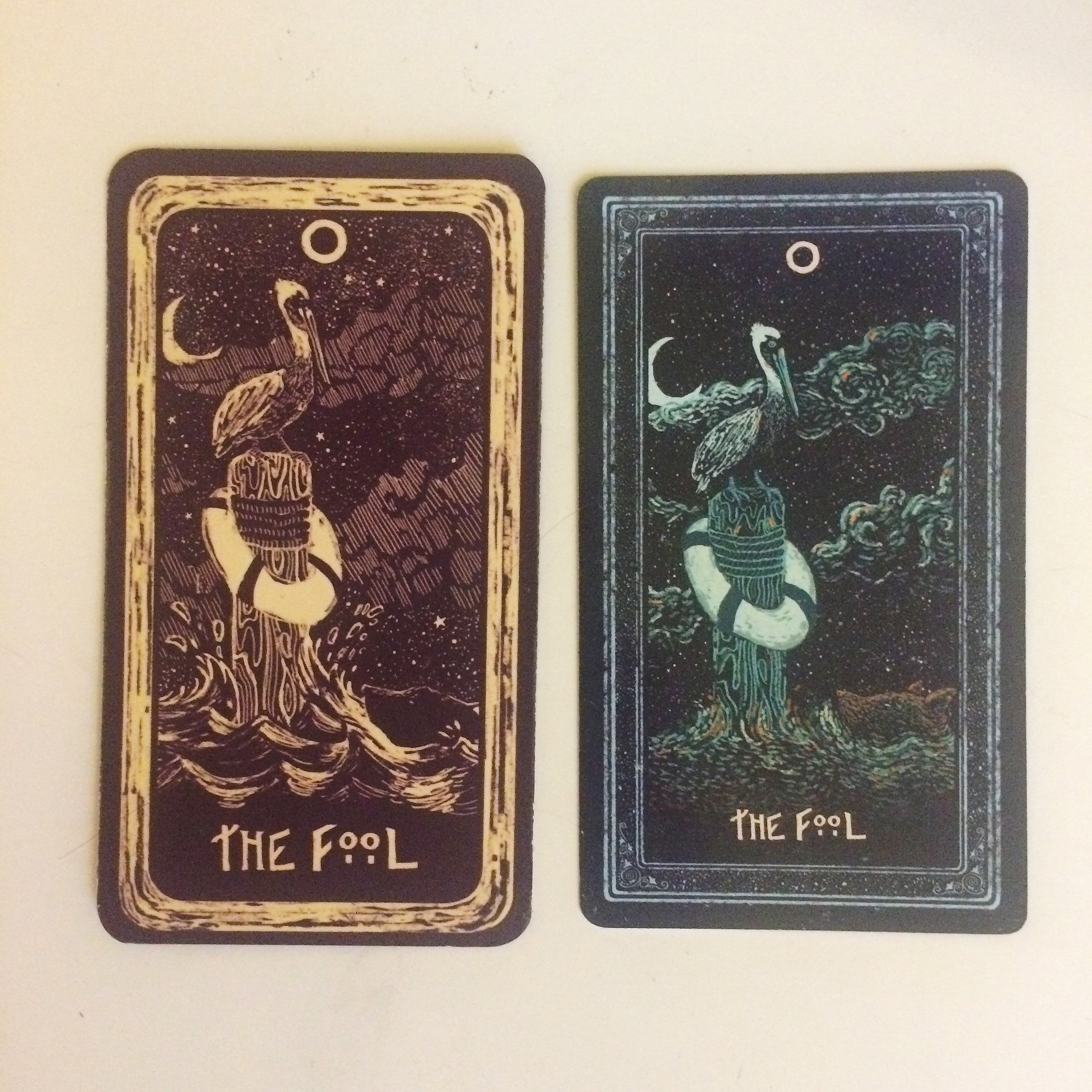 "Depictions of The Fool in James R. Eads' ""Light Visions"" and ""Prisma Visions"" tarot decks. The booklet calls the wolf Foolish for swimming out too far, but I've always thought pelicans were pretty Foolish - they look awkward but fly far."