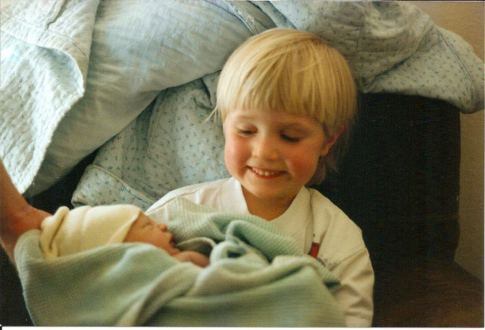 Holding my newborn sister, Sophie, two days after my 5th birthday.