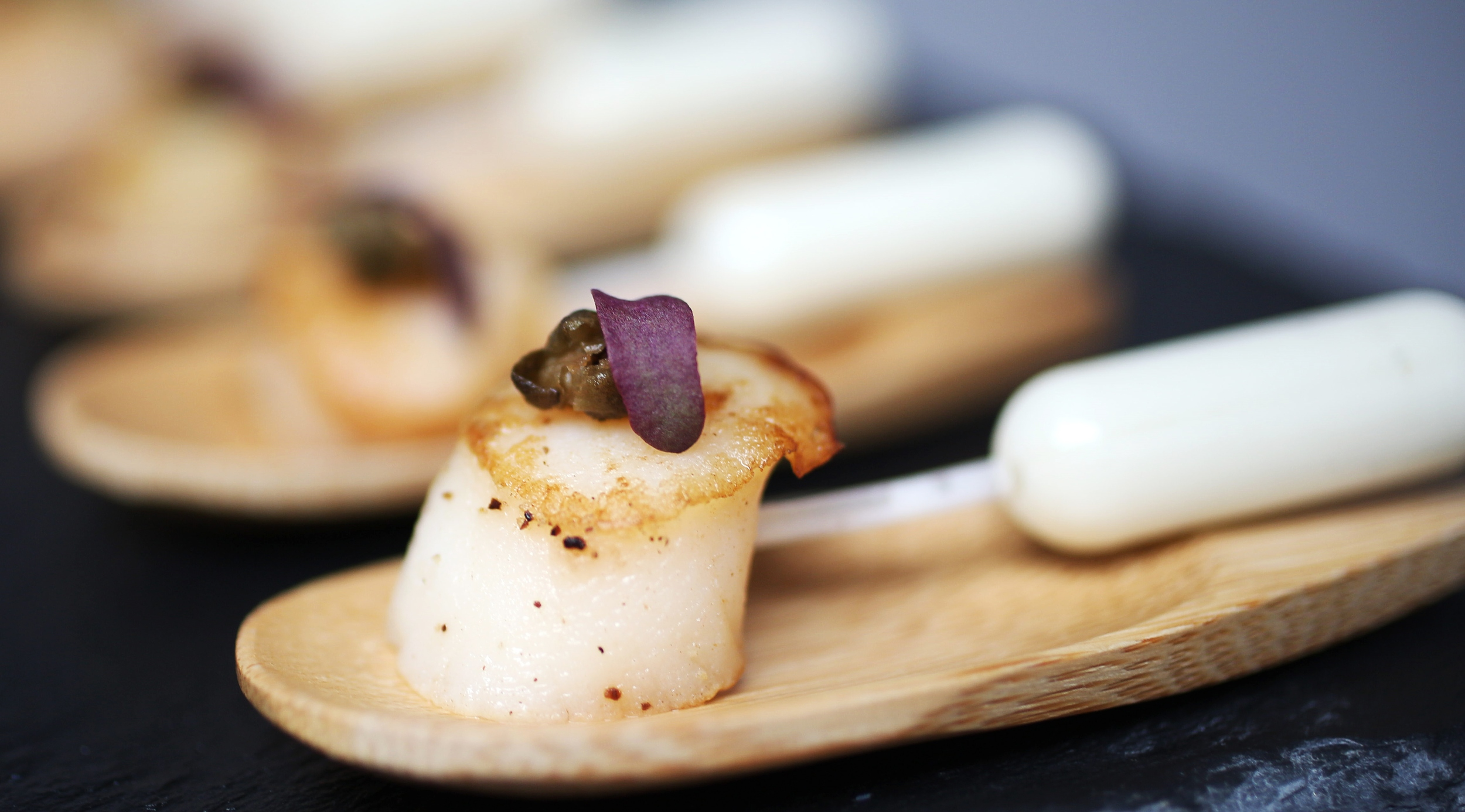 grilled scallops pipettes filled with champagne butter sauce and decorated with red mustard cress.jpg