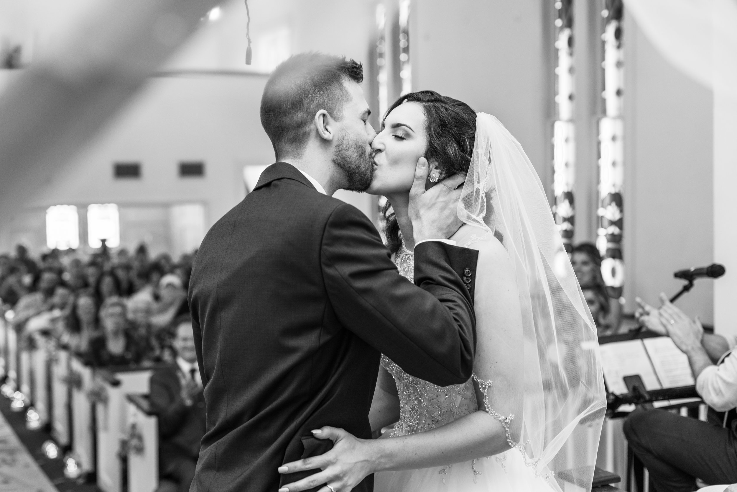 Black and white romantic kissing shot of bride and groom