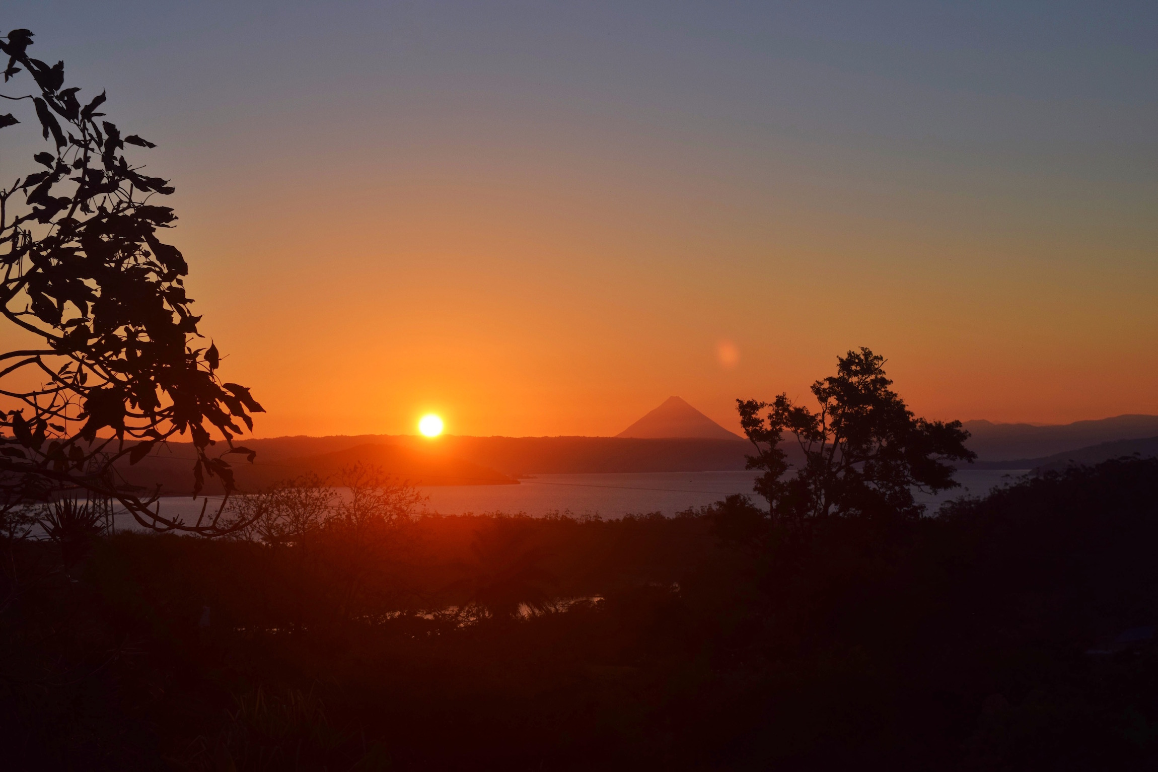Sunrise over Lake Arenal with Arenal Volcano in the distance.  Tessa Juliette   Travel Where to Next http://travelwheretonext.com