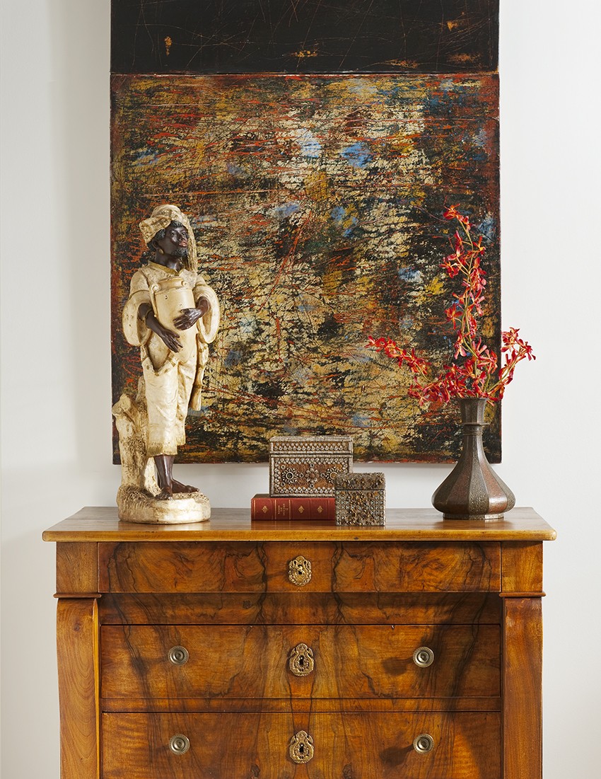 This contemporary painting in a downtown Dallas high-rise matches the earth tones of the items and chest of drawers beneath it.