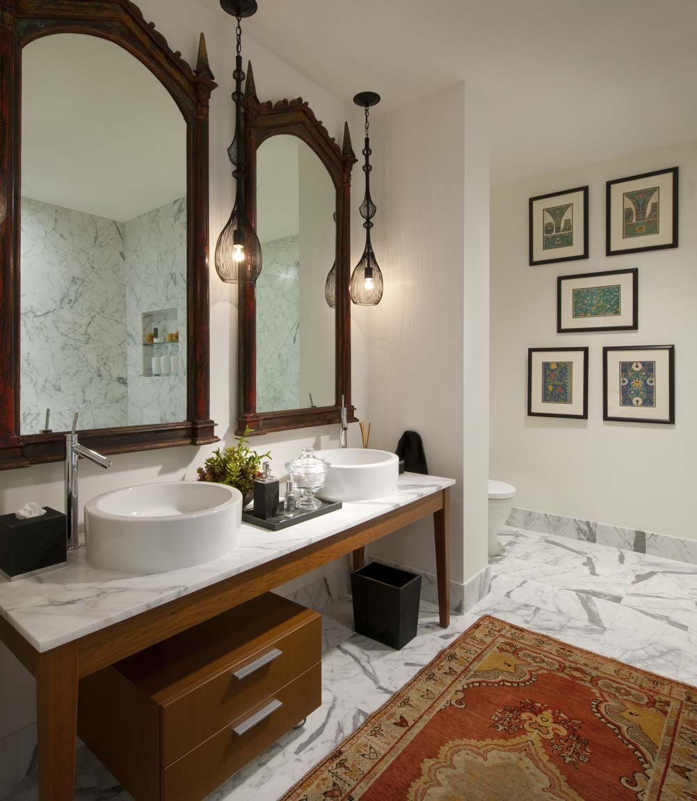 A traditional oriental rug can still belong in a contemporary setting if its colors and pattern complement the rest of the room. The mirrors in this bathroom are also inspired by Indian design.
