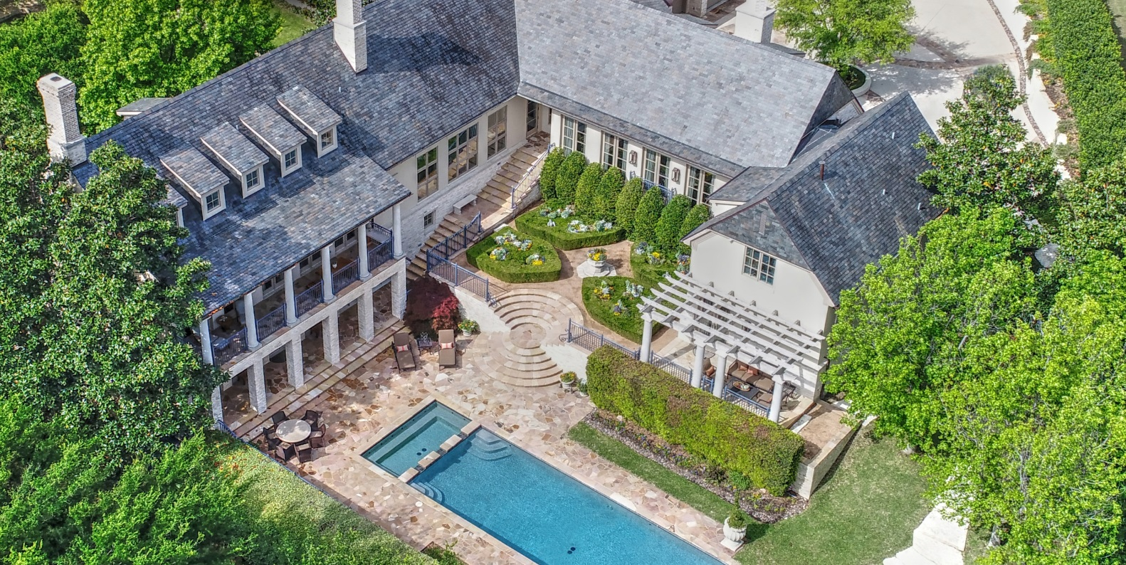 An aerial shot of a Neoclassical home with a double portico in Fort Worth, designed by Ralph Duesing. (This photo is copyright of  Ralph Duesing Architect, LLC . Chambers Interiors & Associates was granted permission to feature this image).