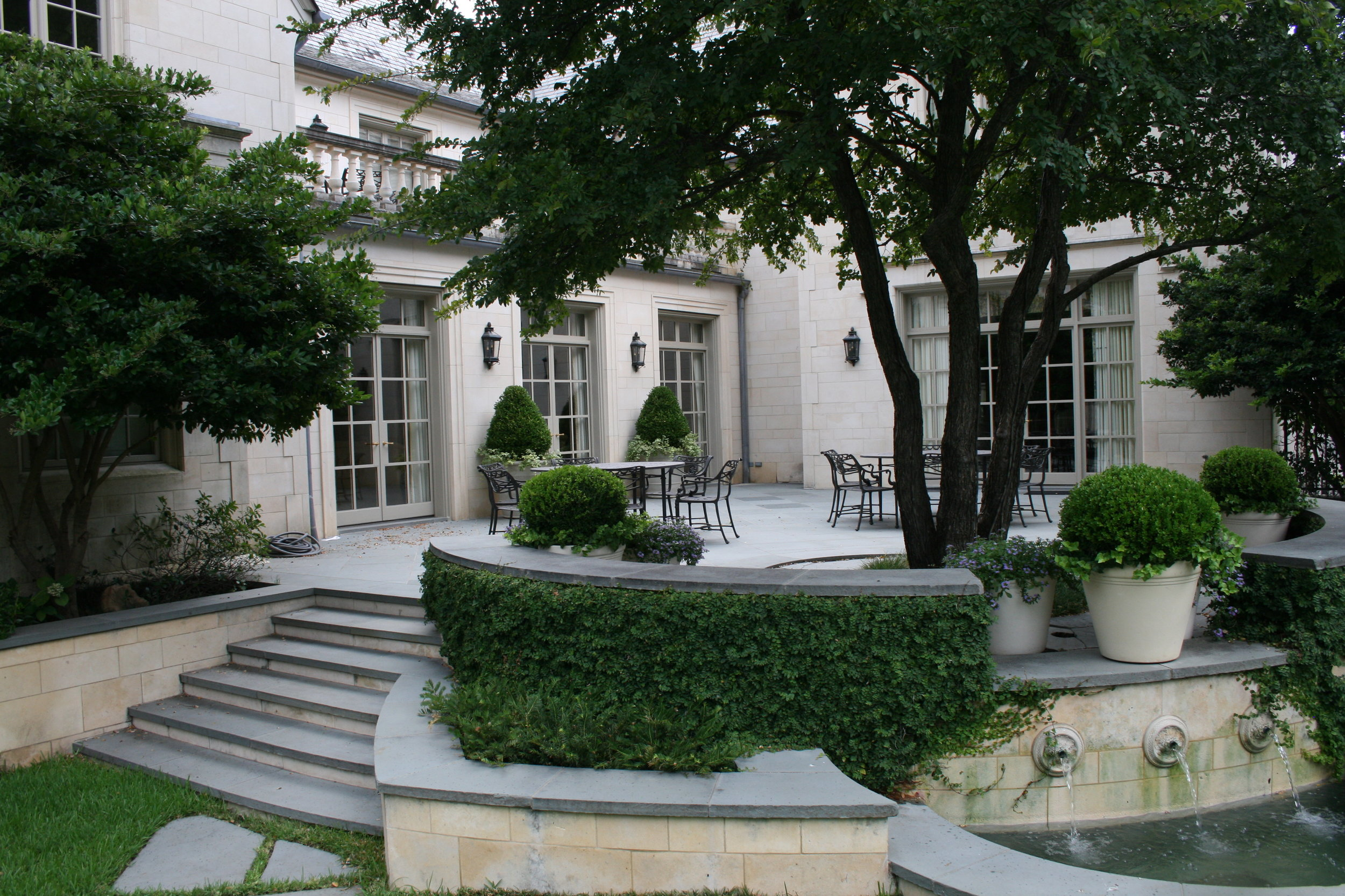 Fountains and abundant greenery give a restful quality to this Neoclassical outdoor area. Paul Turney was the architect for this home, while the landscape architect was  John Armstrong.  (This image is copyright of  Turney & Associates, Inc . Chambers Interiors & Associates was given permission to feature this image).