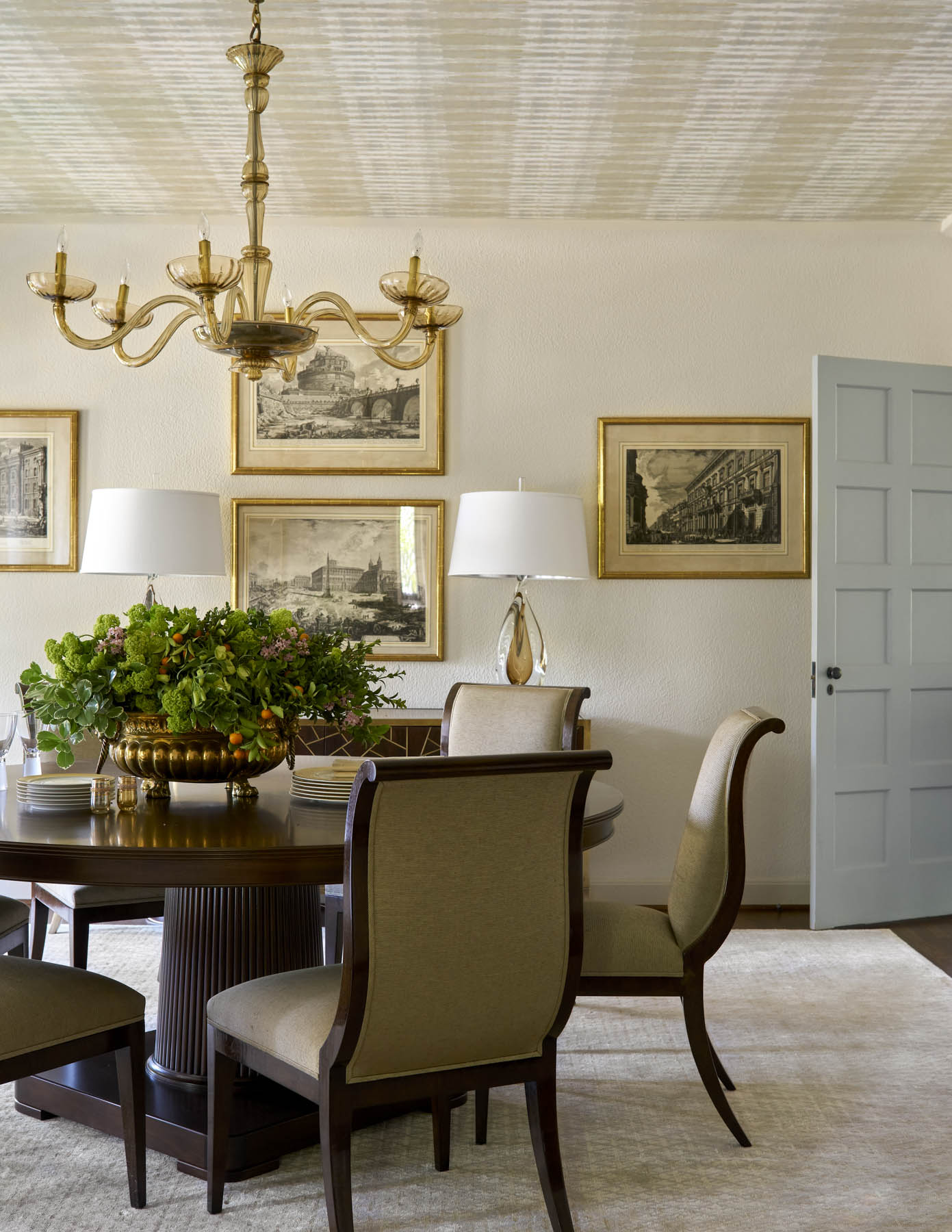 We repainted the walls in the Kessler Park home with mostly neutral colors. In the dining room, beige is a calming backdrop for the gold-framed antique prints. Before, the ceiling was also a dark terracotta color. Covering it with a light wallpaper helped the room feel more expansive.