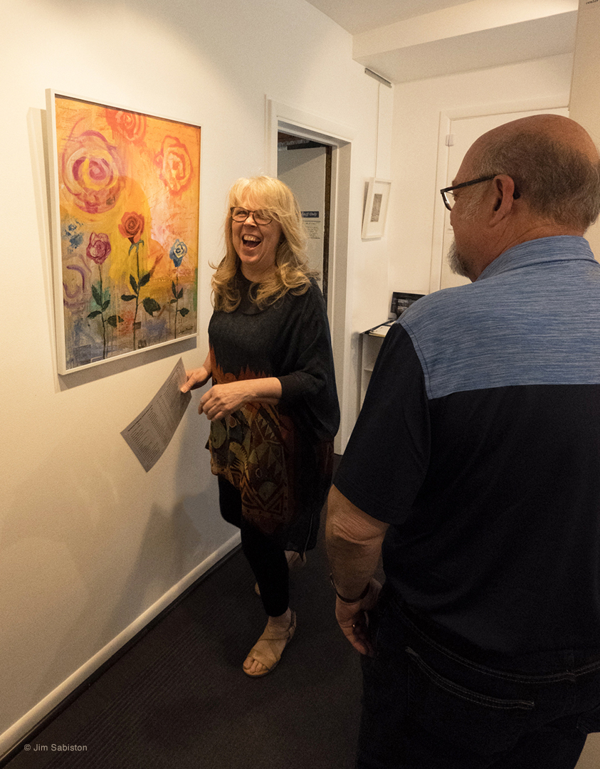 "Photographer, Pamela Waldroup always having fun and smiling for the camera.  Shown is ""One Perfect Rose-1 for Dorothy Parker"" - oil and collage on paper by artist, Lucy Dewitt."