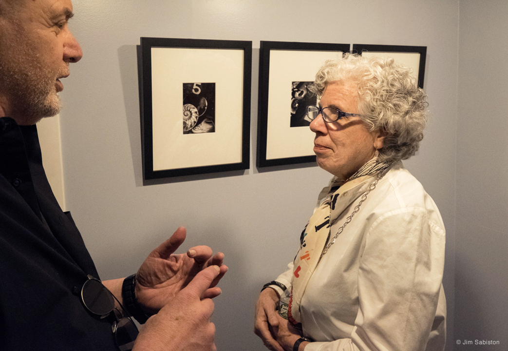 "Artists, Richard Gardner and Karen Bell talking shop. Shown on the wall are works by Gardner's ""Flying Eggplant #5"" series."